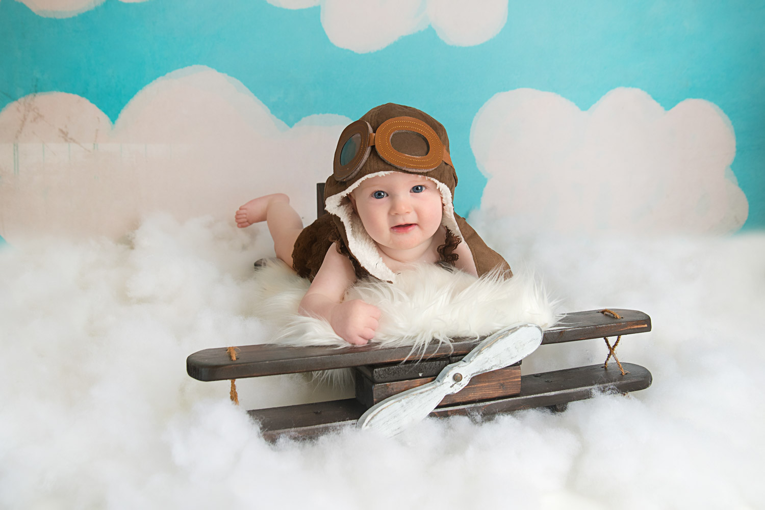 st-louis-baby-photographer-6-month-girl-on-wooden-plane-with-avaitor-hat-and-clouds.jpg