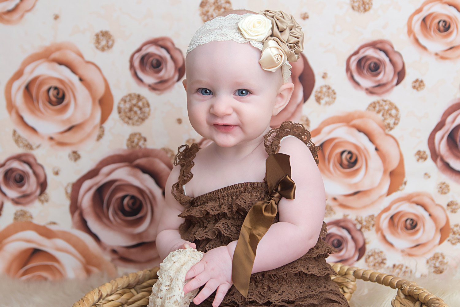 st-louis-baby-photographer-6-month-session-girl-in-lace-romper-on-rose-backdrop.jpg