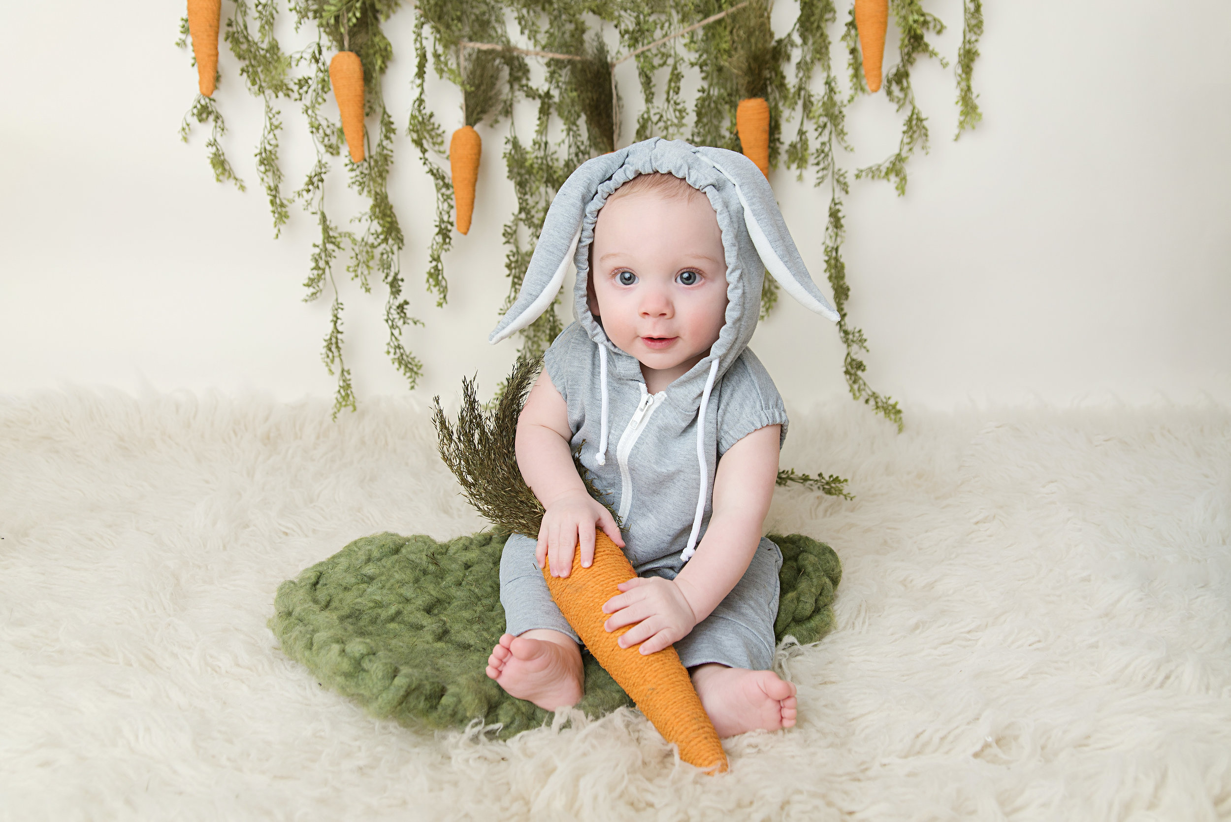 st-louis-baby-photographer-baby-boy-in-bunny-romper-with-green-bunting.jpg