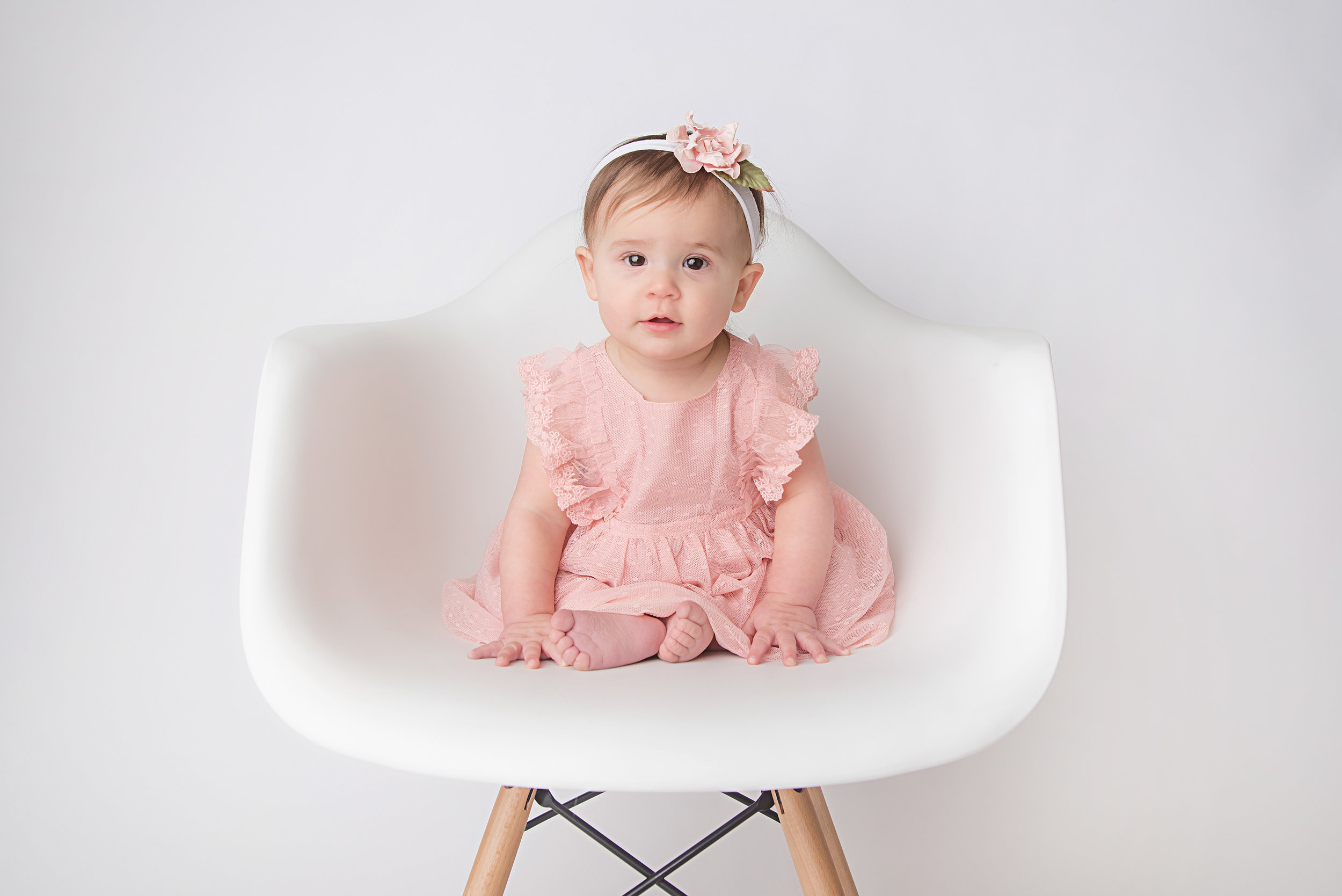 st-louis-baby-photographer-sitting-milestone-session-baby-girl-in-pink-dress-sitting-in-white-chair.jpg