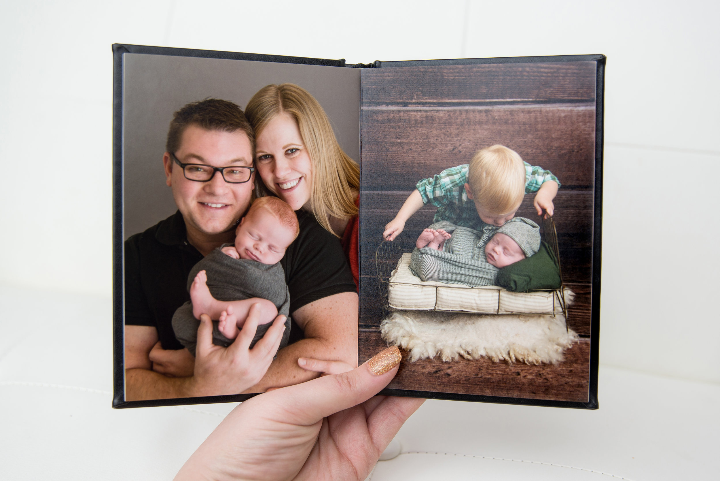 st-louis-photographer-the-session-book-hand-holding-book-open-showing-newborn-session-images.jpg