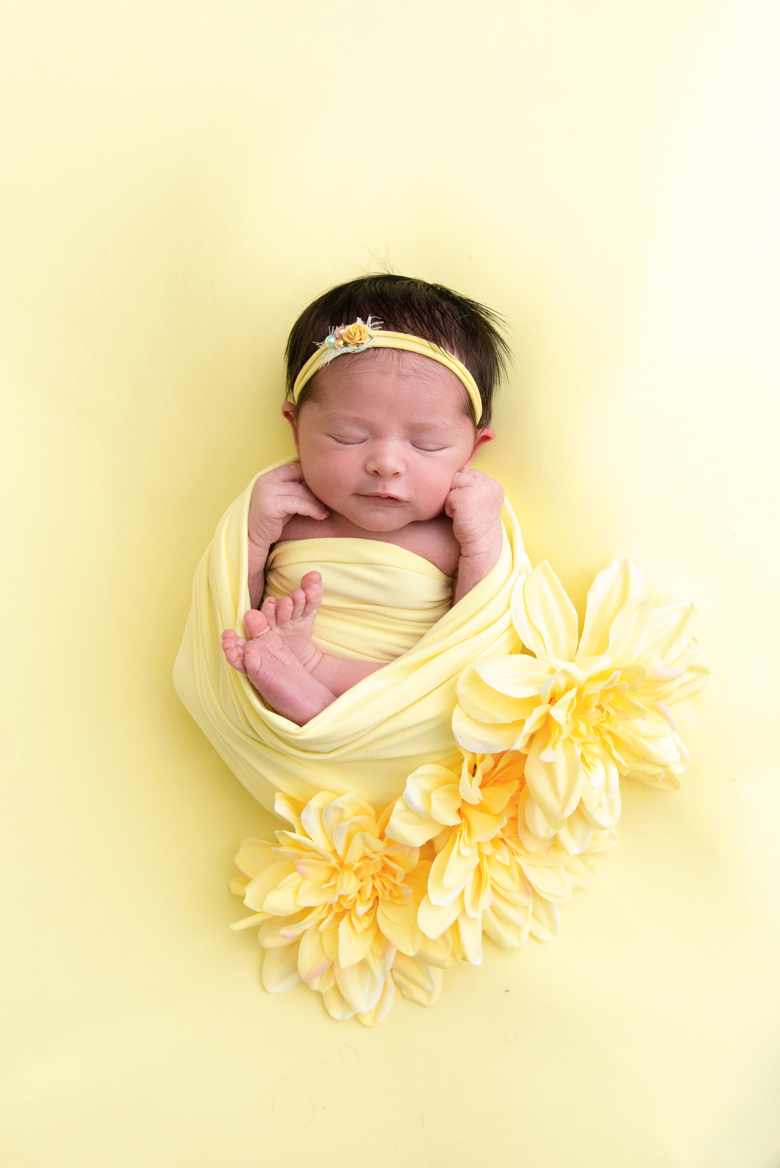 st-louis-newborn-photographer-baby-girl-with-dark-hair-on-yellow-backdrop-with-yellow-flowers.jpg