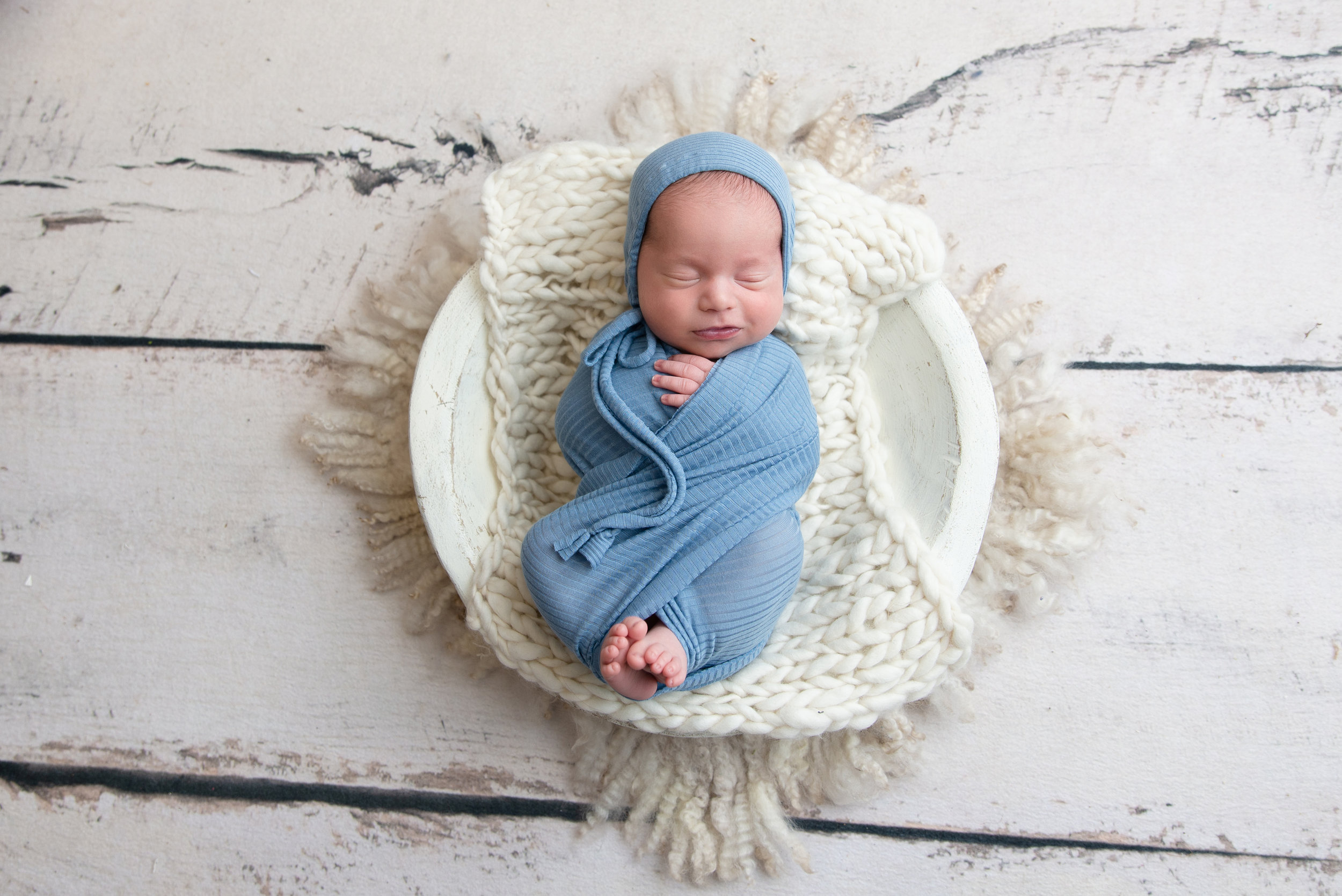 st-louis-newborn-photographer-baby-boy-wrapped-in-light-blue-smiling-on-white-floor.jpg