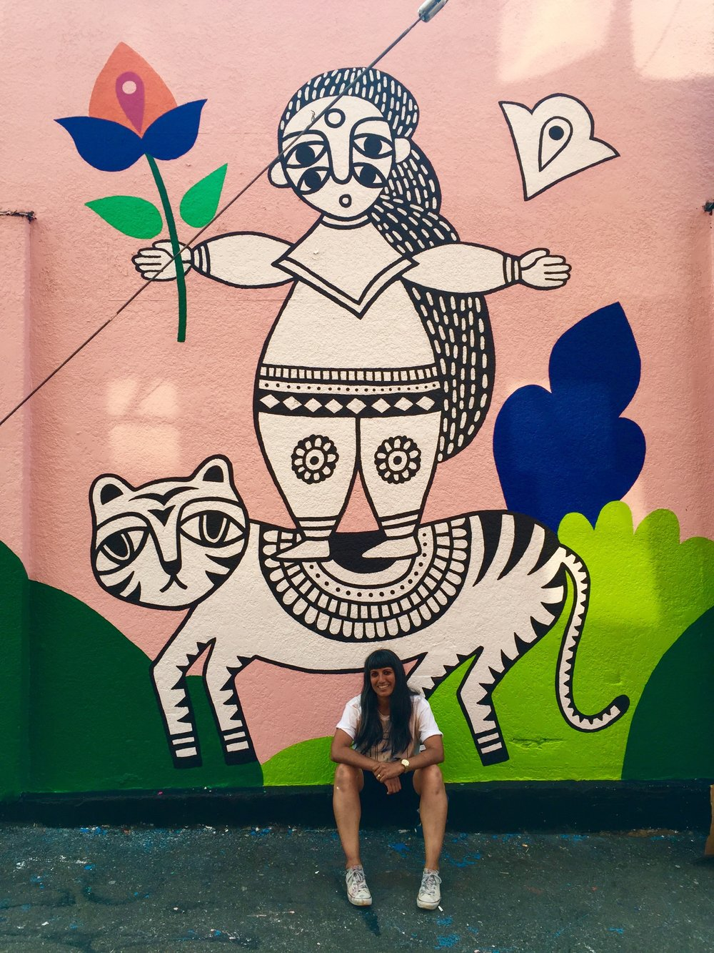 PHOTO CREDIT:  Megan Jenkins    Chats with Sandeep Johal @ Her mural: GIRLS ARE FIERCE LIKE TIGERS    I've lived in Mount Pleasant for over a decade. I currently live a few blocks away from my mural, which is located at a transit hub I use pretty consistently. To see it on an almost daily basis is pretty special.  It was important to me that the mural had a South Asian aesthetic to reflect my heritage. There are so few South Asian artists here (for many reasons, but the main one being artists aren't encouraged in my culture) and I wanted it to inspire other South Asians who are aspiring to work in the arts.The lady on the tiger originally came from a drawing I did at a residency at the Anvil Centre in New West last year.   Favourite things about painting the mural?   One of the best parts of painting this mural was meeting so many South Asians who came by to say hi and support me. I felt honoured to be painting a mural for VMF and scared, nervous about such a big wall, especially since it was my first outdoor mural. But, I did it, with the assistance from friends, and now all I want to do is paint murals all over the place — walls, ceilings, floors, stairs, wherever. I feel so much more confident. The press I got during the mural fest has also led to different opportunities and helped me propel my career forward, which I'm eternally thankful for.  The fact that VMF exists is a win. Supporting local talents, exposing the larger community to artists, giving everyone access to public art, and beautifying otherwise bland or under-utilized spaces is only some of what VMF is doing to make Vancity better. The fact that VMF is working towards 50% of the artists being female, supporting Indigenous artists, and first time muralists is pretty awesome. Oh, and the artists get paid! :)