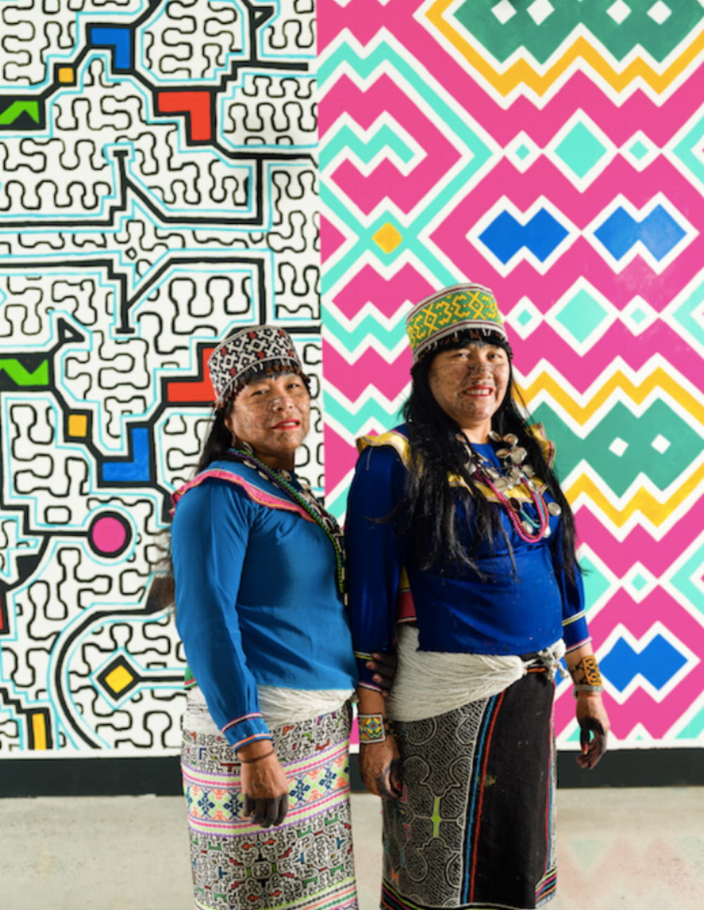Photo:  Alina Ilyasova / MOA    Peruvian Artists Bring Kené Design to Vancouver   Olinda and Silvia are Indigenous artists from the Peruvian Amazon's Ucayali River region. They belong to the Shipibo-Conibo diaspora, relocating to Lima Peru in the 1990s.  Both women began working as artists in 2016 and specialize in Kené, an ancestral, women-only, art form. Those who train in Kené learn to dream and see designs in their minds and transcribe the patterns they imagine onto the skin as tattoos, textiles, and other mediums. When a woman learns how to materialize these designs, her abilities are considered sacred.  Not only is the art form passed down from generation to generation, but it has cultural and mythological significance in Shipibo-Conibo culture. Its geometric designs resemble patterns and systems found in nature including snakeskin, constellations, the forest, and the Amazonian river. These strong ties to nature reflect people's relationship with all-powerful gods that sustain their communities and surrounding natural environments.  While Olinda and Silvia's designs can be seen on the walls of Lima Peru, their installation at the Museum of Anthropology and mural on Granville Island, is the their first ever international project. This opportunity has led to new possibilities for the artists who have been invited to paint and share their experiences in other parts of the world.