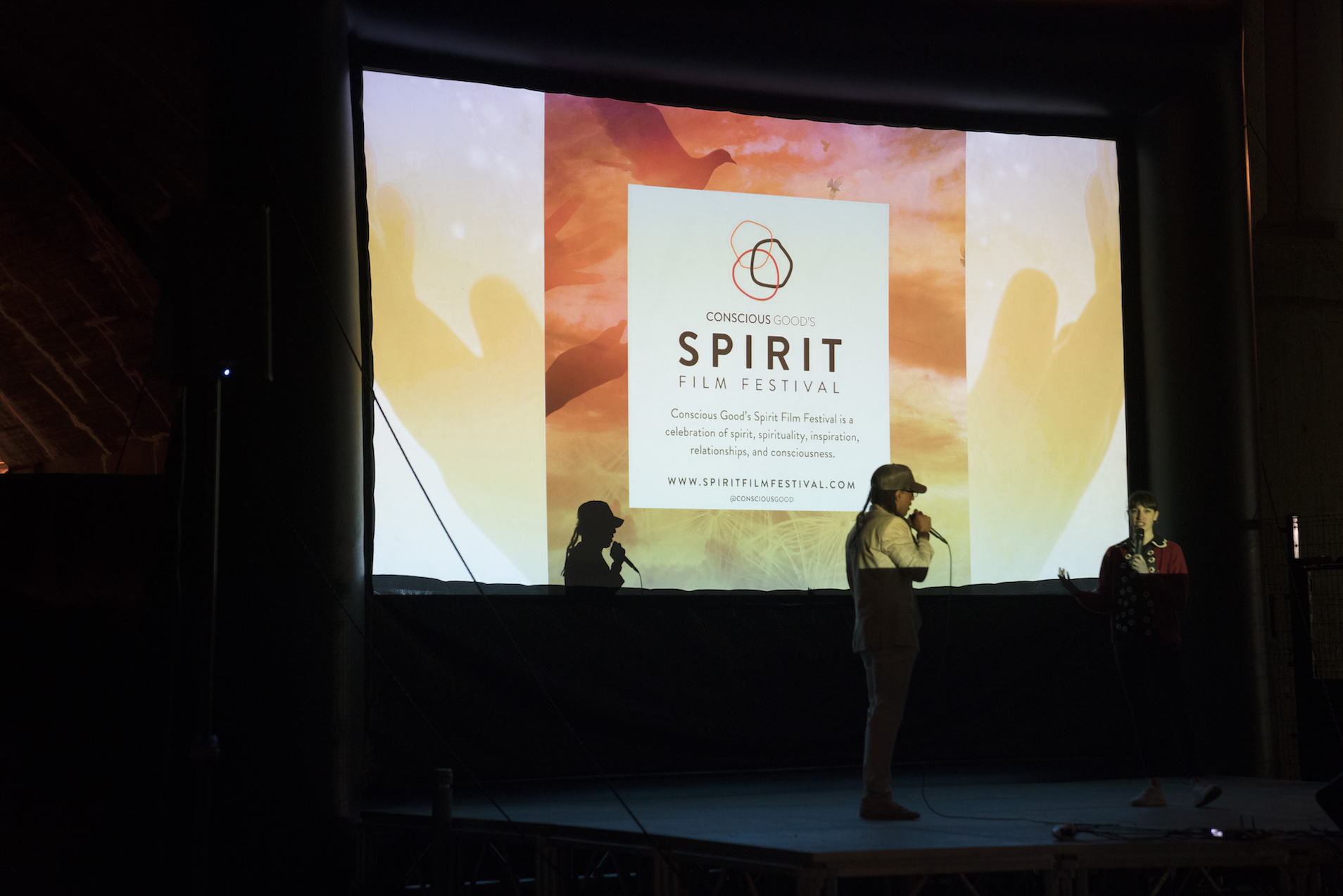 Jacques and Emily Ann on stage with Spirit Film Fest logo.jpeg