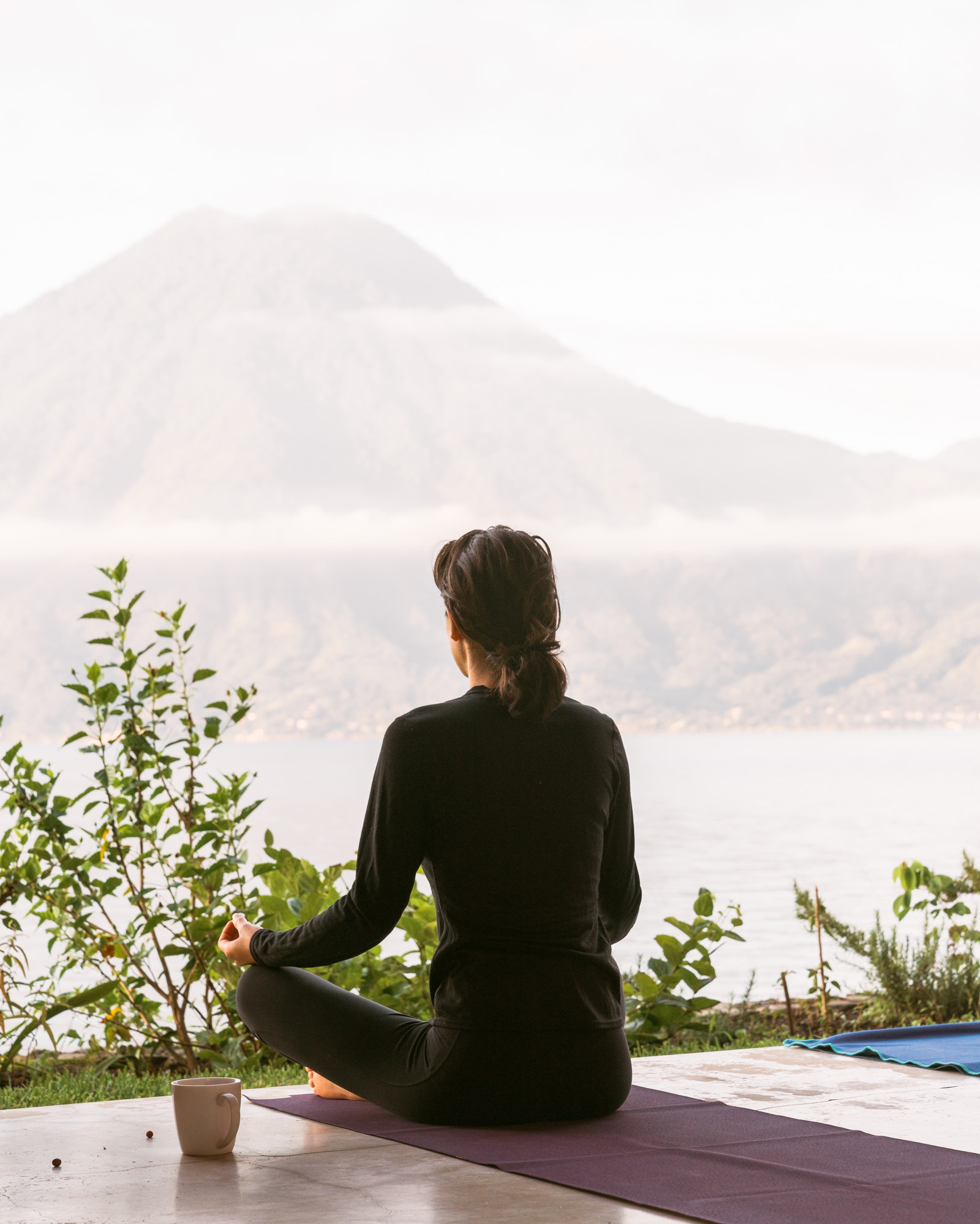 Woman meditating in front of the water at lake atitlan