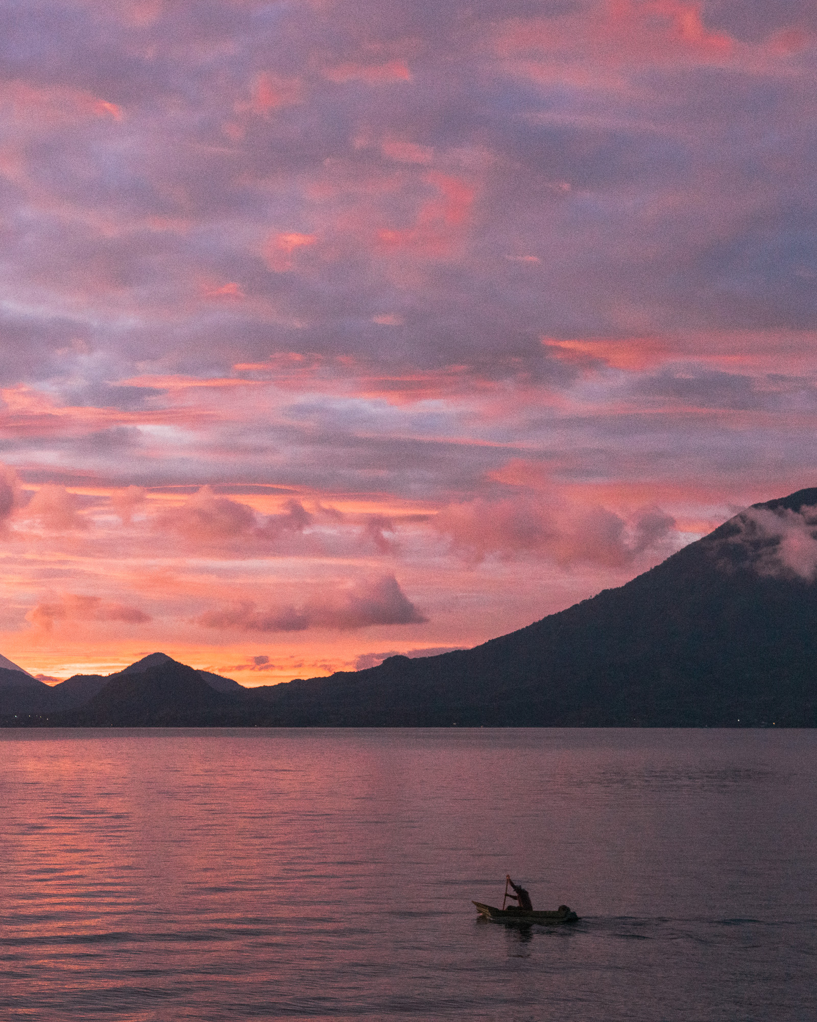 Sunset at Lake Atitlan with a view over the Water and a local fischerman