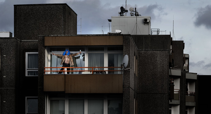 Hermann (in blue wig, leopard coat, and no shirt) with arms extended wide on an apartment balcony. (photo: Sven Hagolani)