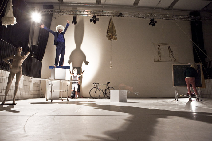 Müller, in white curly wig, stands atop a box and cart, reaching wide. Curtis' shadow fills the white wall behind him. (photo: Sven Hagolani)