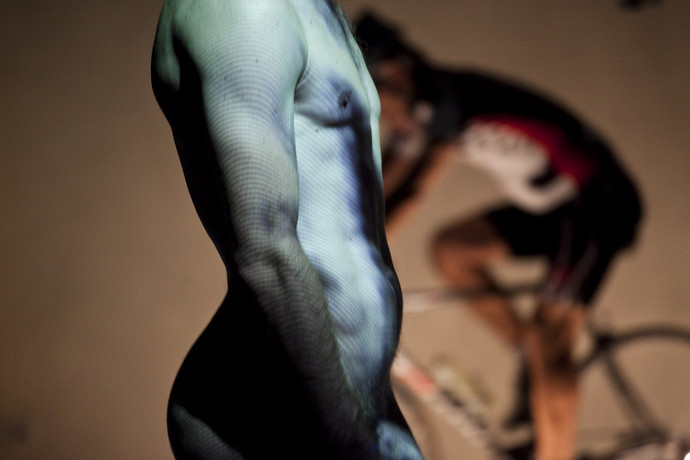 Torso shot of nude male lit by projections, with Curtis on bike in background. (photo: Sven Hagolani)