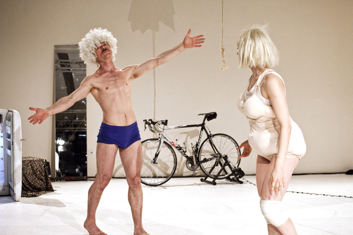 Müller, in curly white wig, spreads arms toward Scaroni, in padded body suit and blonde wig. (photo: Sven Hagolani)