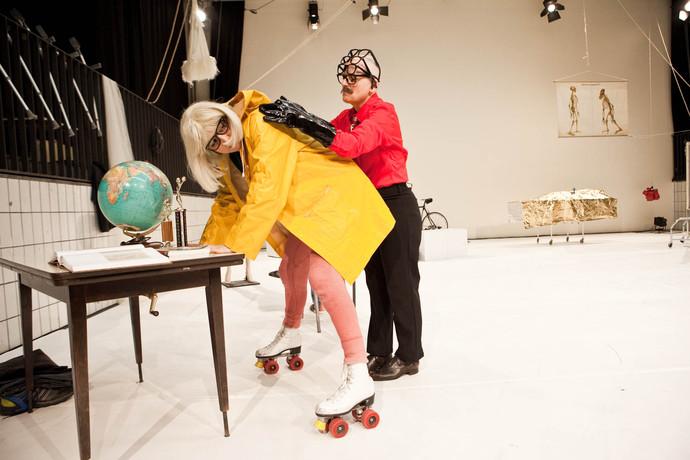 Scaroni, in slicker and skates, hunches over school desk. Markland presses up behind her. (photo: Sven Hagolani)
