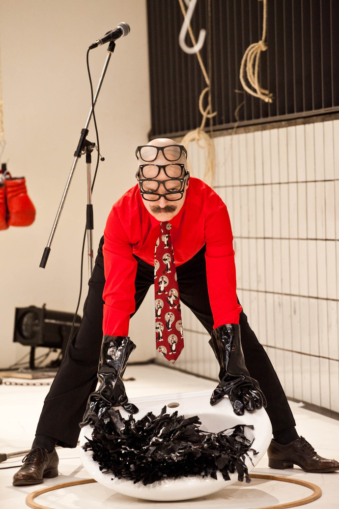Markland straddles a porcelain sink that lies on the floor. A red cartoon necktie dangles as he looks into the camera. (photo: Sven Hagolani)