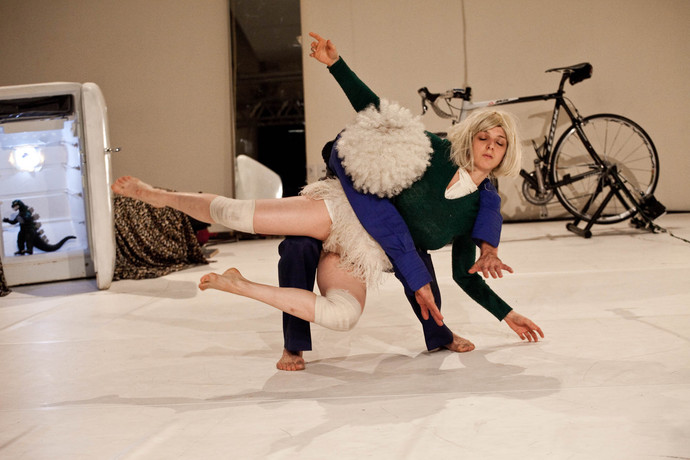A contact improv moment in white wigs: Müller suspends Scaroni on his thighs; Scaroni closes eyes. (photo: Sven Hagolani)