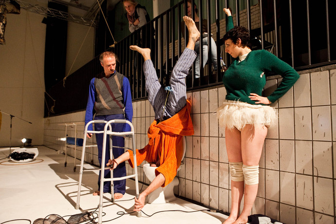 Curtis, in pajamas, stands on his head inside a toilet bowl using a walker to balance. Müller & Scaroni look on. (photo: Sven Hagolani)