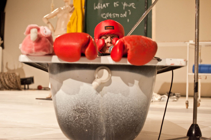 Cunningham, eyes closed, sits in bath tub with red wrestling helmet and gloves. (photo: Sven Hagolani)