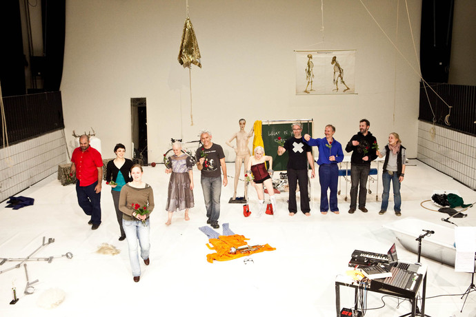 Cast and crew take a bow on cluttered stage. Some hold red flowers. (photo: Sven Hagolani)