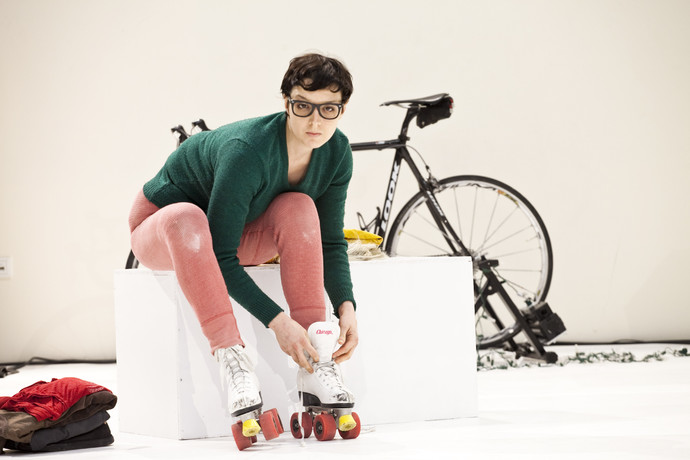 Scaroni, with short brown hair & glasses, adjusts her roller skates. Behind her is a black bicycle. (photo: Sven Hagolani)