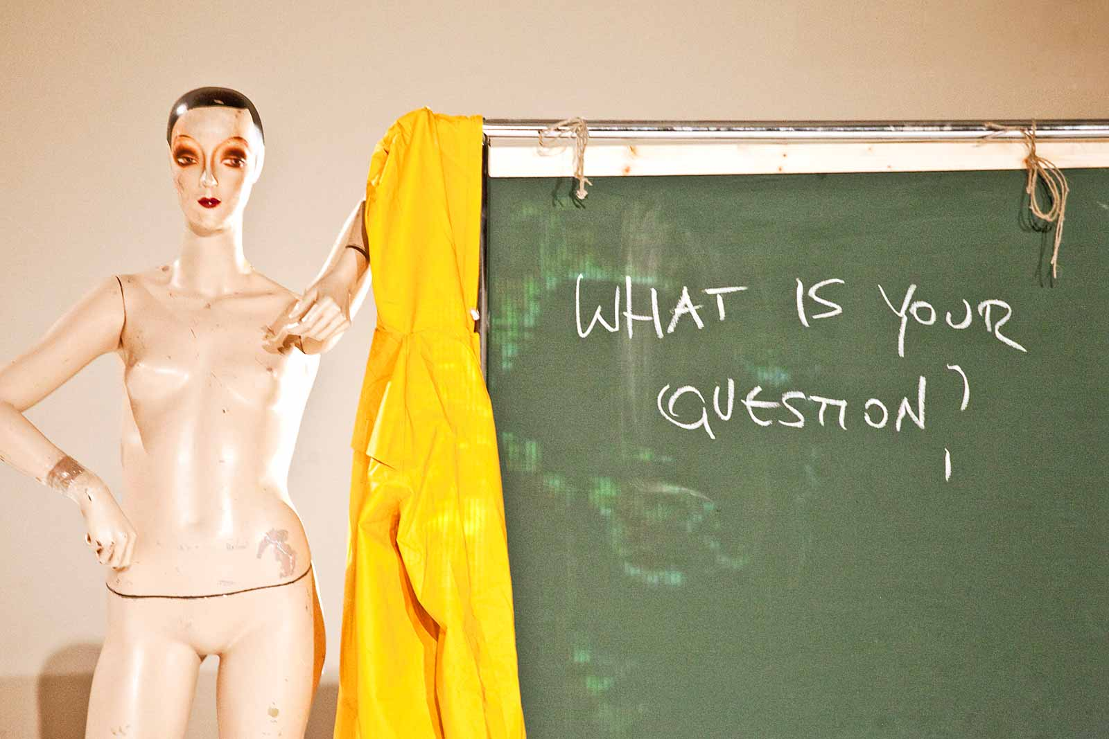 """Vintage mannequin leans jauntily against chalkboard on which is written: """"What is your Question?"""" (photo: Sven Hagolani)"""