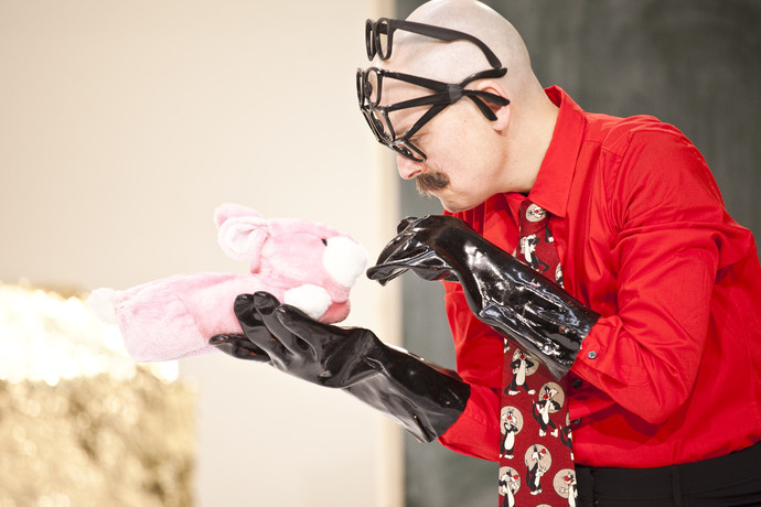 Markland, wearing large black rubber gloves, holds a pink bunny slipper as if allowing it to sniff his fingers. (photo: Sven Hagolani)