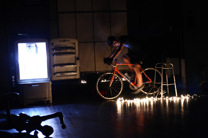 Curtis in pro bicycle costume pedals a bike in the dark. An open refrigerator glows from within. (photo: Kristine Slipson)