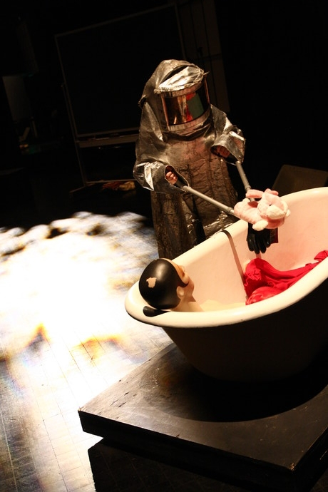 On dim stage, Cunningham in oversized silver hazmat suit holds pink bunny slipper over bath tub from which upper torso of vintage mannequin protrudes. (photo: Kristine Slipson)