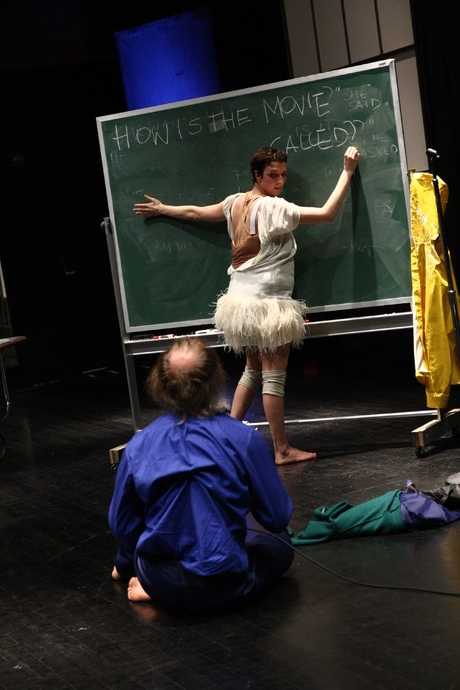 """Scaroni, in white half-zipped costume, writes """"HOW IS THE MOVIE CALLED"""" on chalkboard. Müller watches. (photo: Kristine Slipson)"""