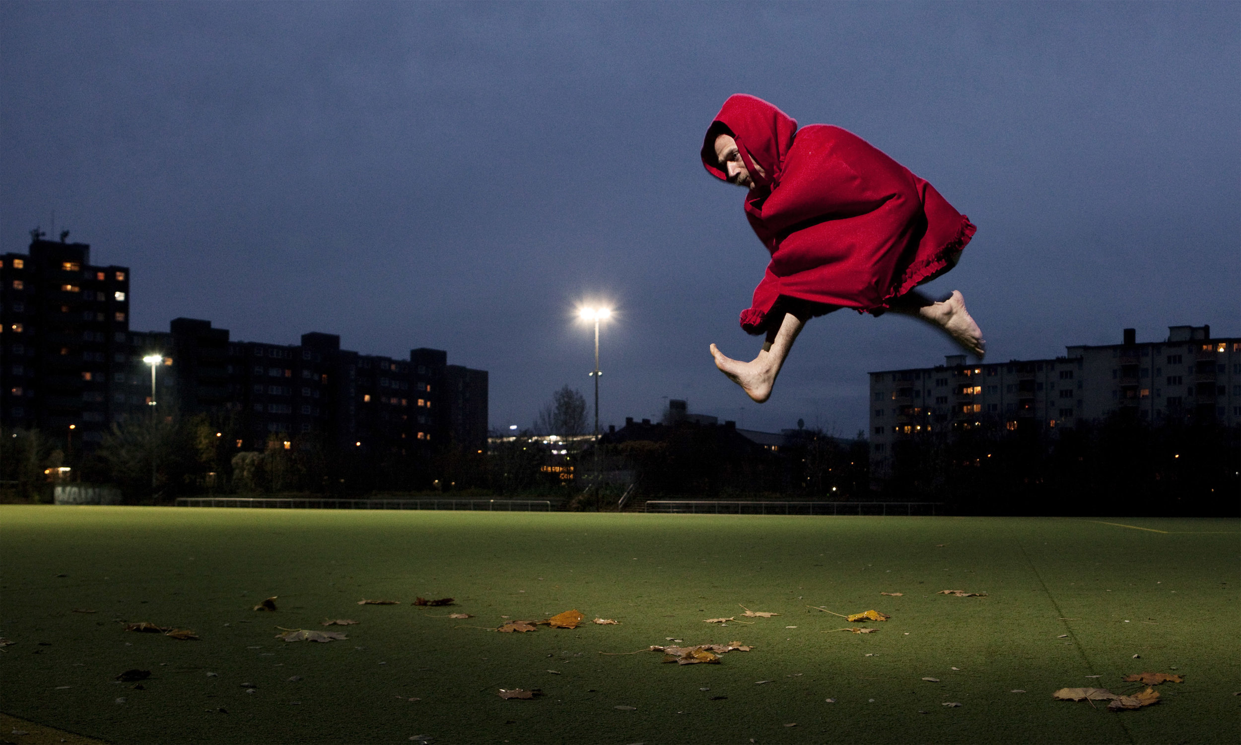 Müller, in Little Red Riding Hood cloak and bare feet, leaps over a grassy park at night. (photo: Sven Hagolani)