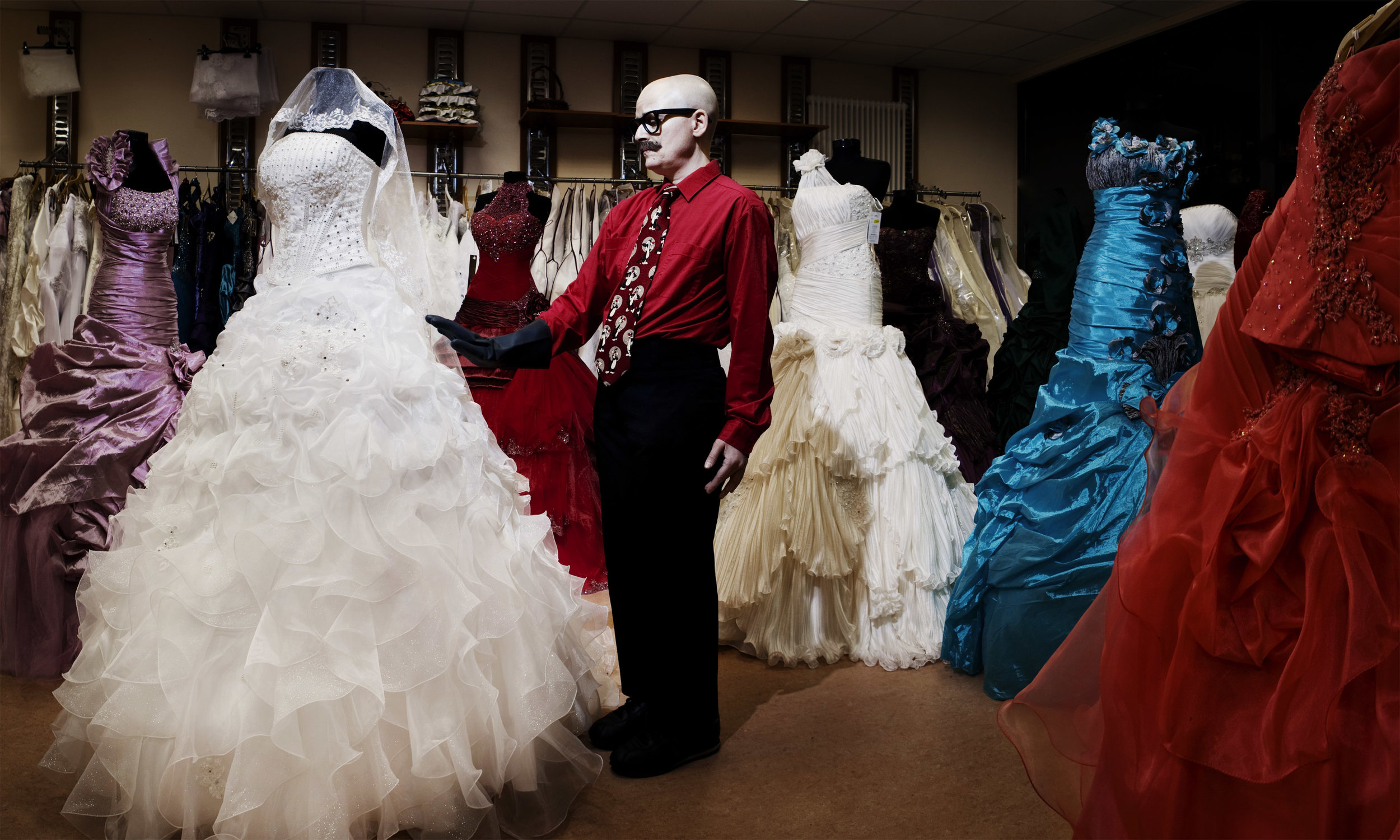 Markland (a slight, bald figure with fake moustache and glasses) stands in a room full of ball gowns. (photo: Sven Hagolani)