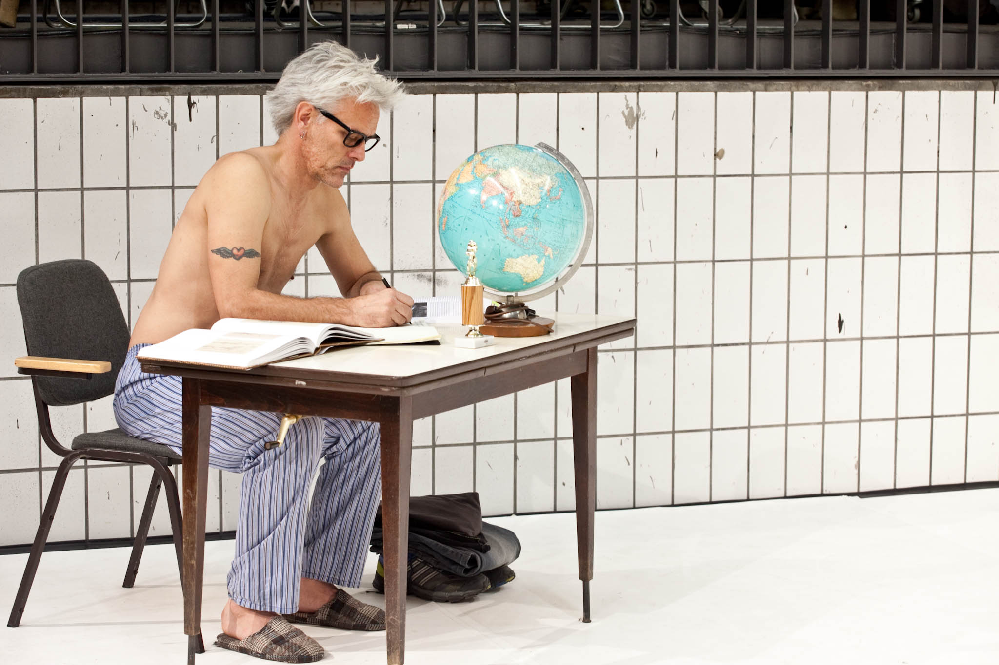 Curtis, in pajama pants with silver hair and glasses, writes at a wooden desk, with a globe, trophy, and open book. (photo: Sven Hagolani)
