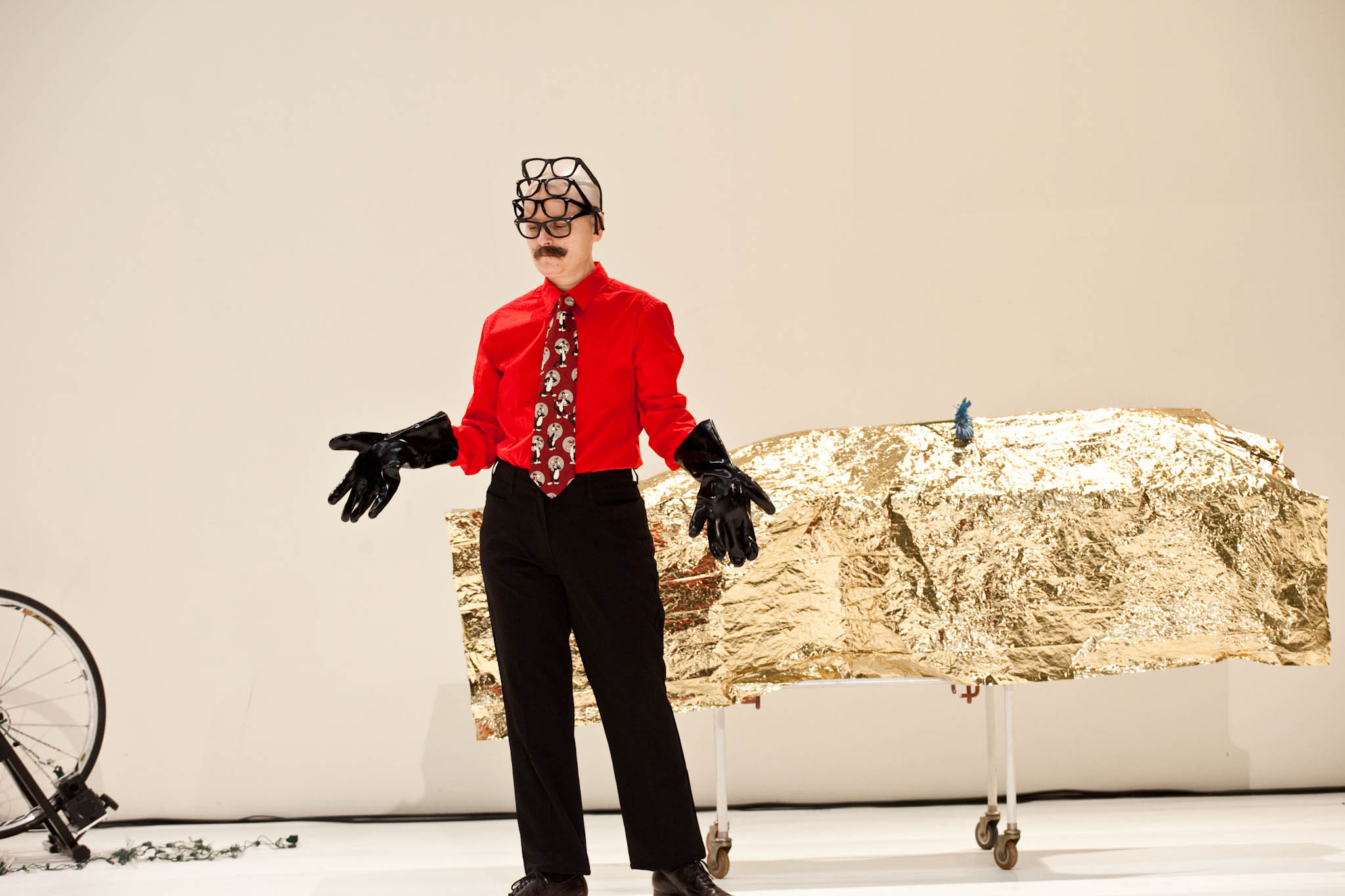 Markland, in 4 stacked eyeglasses and black rubber gloves, gestures before the gold-draped gurney. (photo: Sven Hagolani)