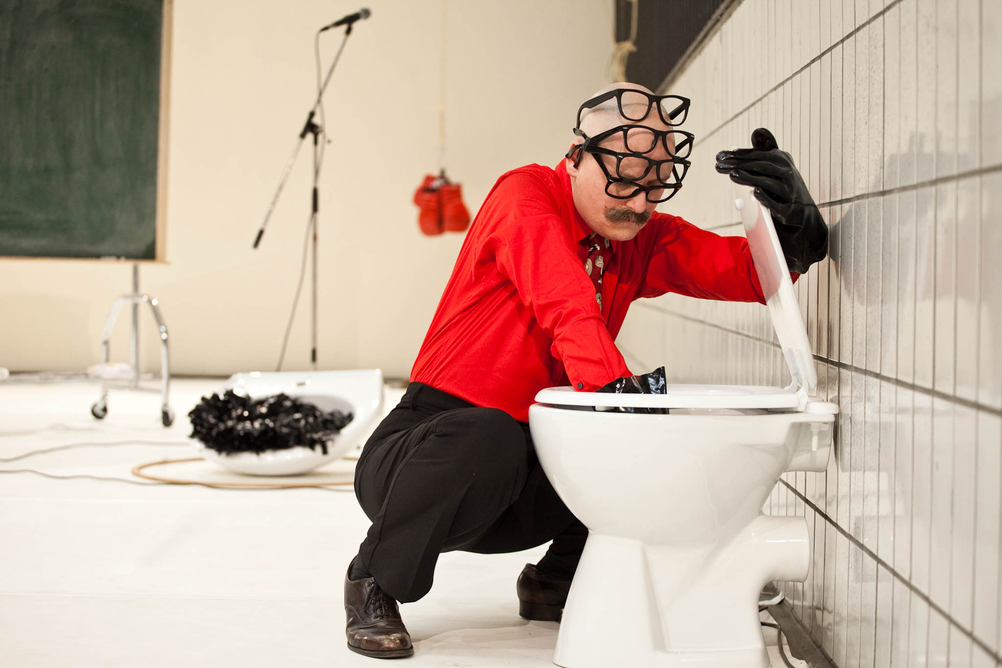 Markland reaches into a toilet bowl. A porcelain sink filled with shiny black material sits in the background. (photo: Sven Hagolani)