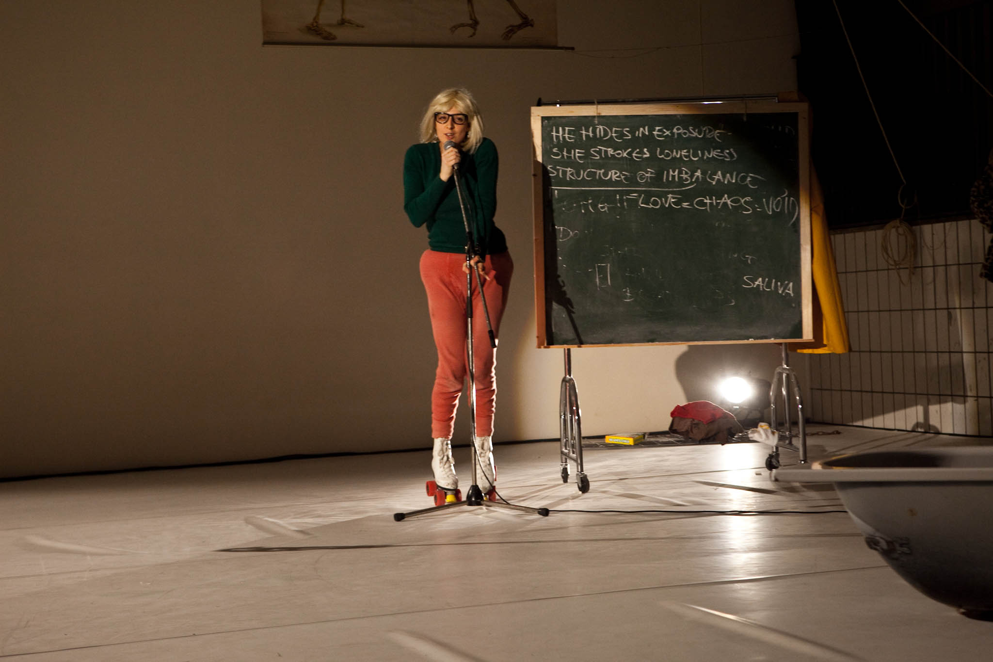 """Scaroni on mic. Chalkboard reads """"HE HIDES IN EXPOSURE / SHE STROKES LONELINESS / STRUCTURE OF IMBALANCE / LOVE CHAOS VOID / SALIVA"""" (photo: Sven Hagolani)"""