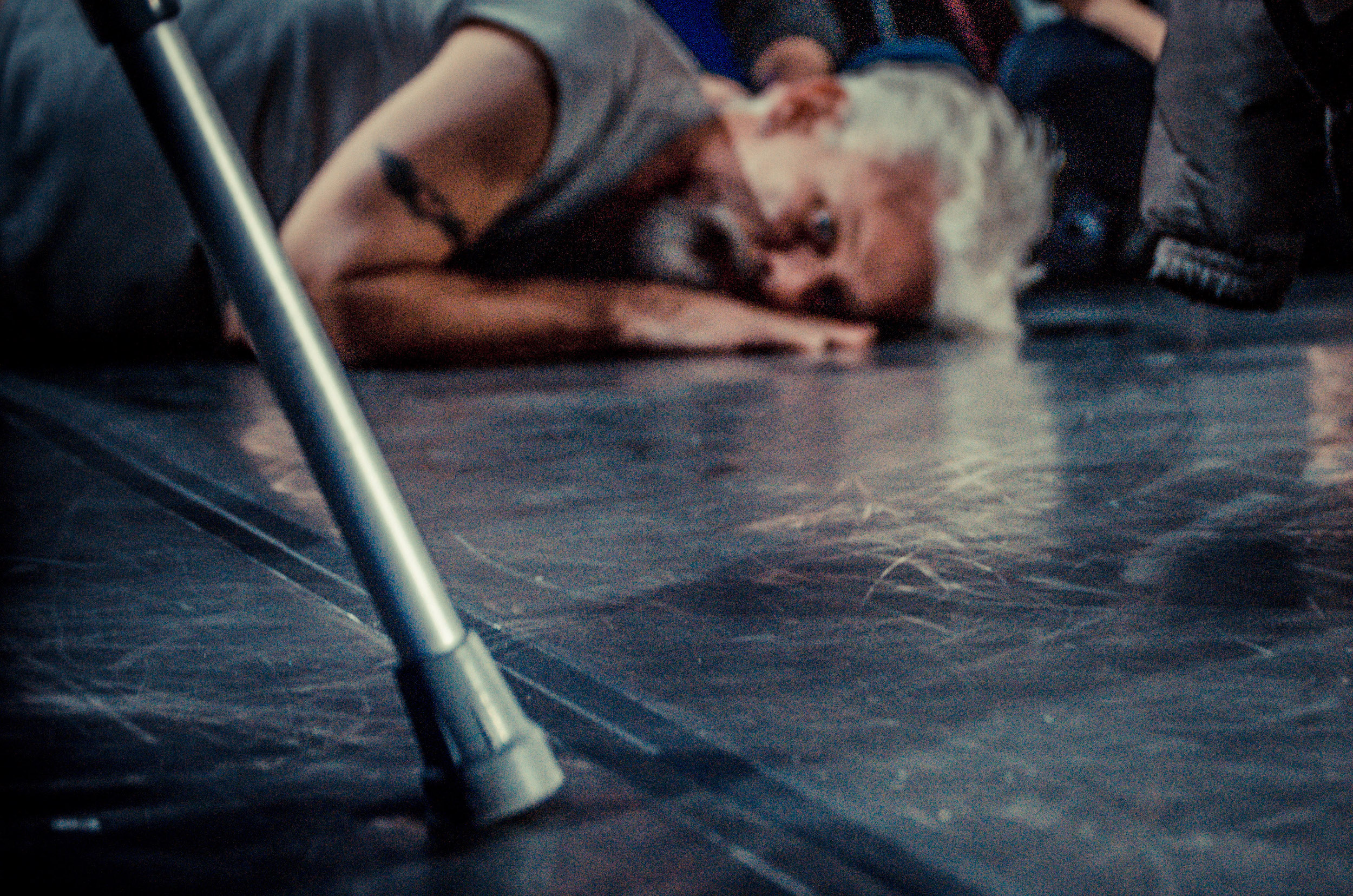 Curtis (out of focus in background) lies facedown on dance floor, looks toward camera. Base of a crutch in foreground. (photo: Robbie Sweeny)
