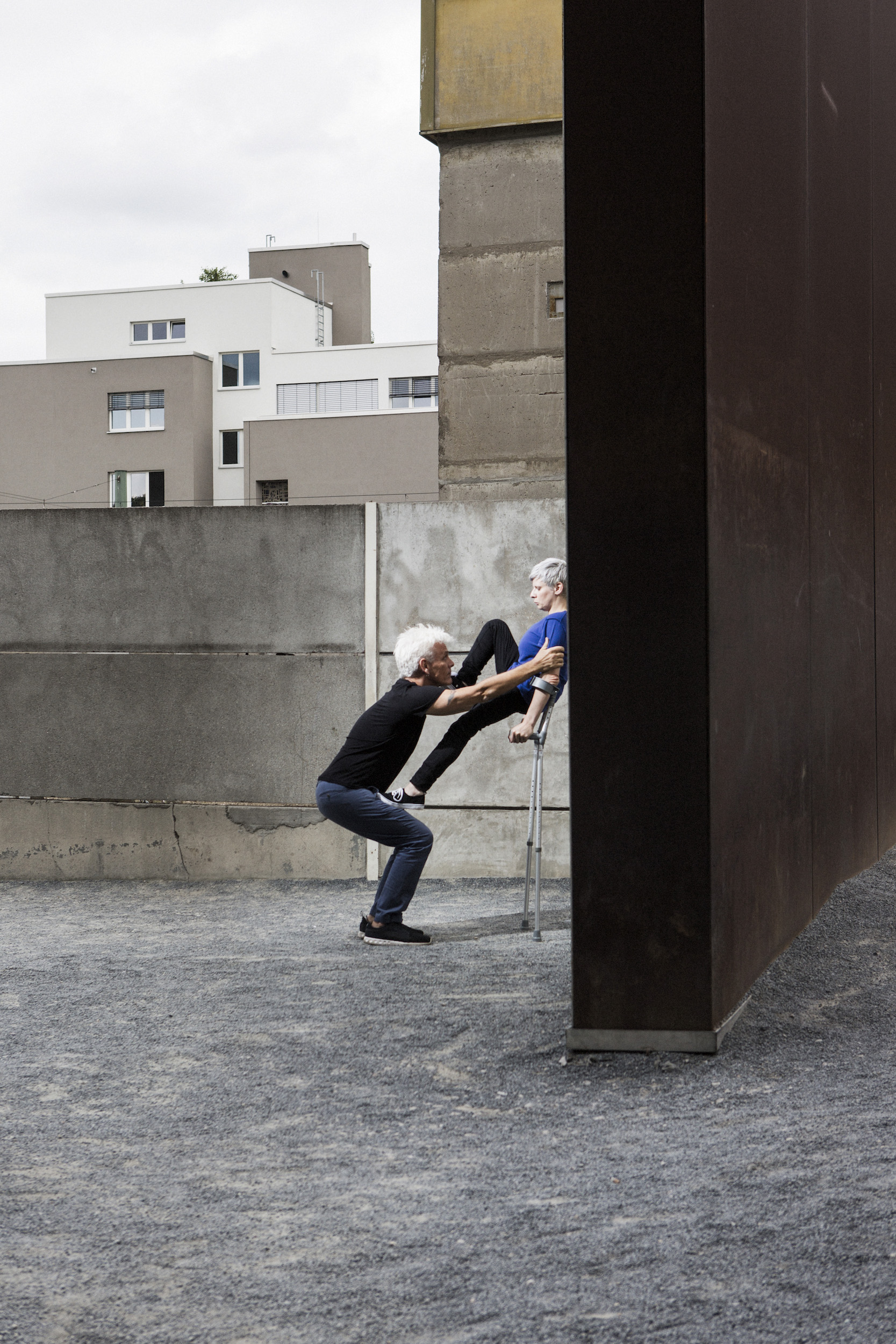Cunningham presses back against a massive brown wall in a spare, urban space, stepping on Curtis' thigh and shoulder, as he supports her. (photo: Sven Hagolani)