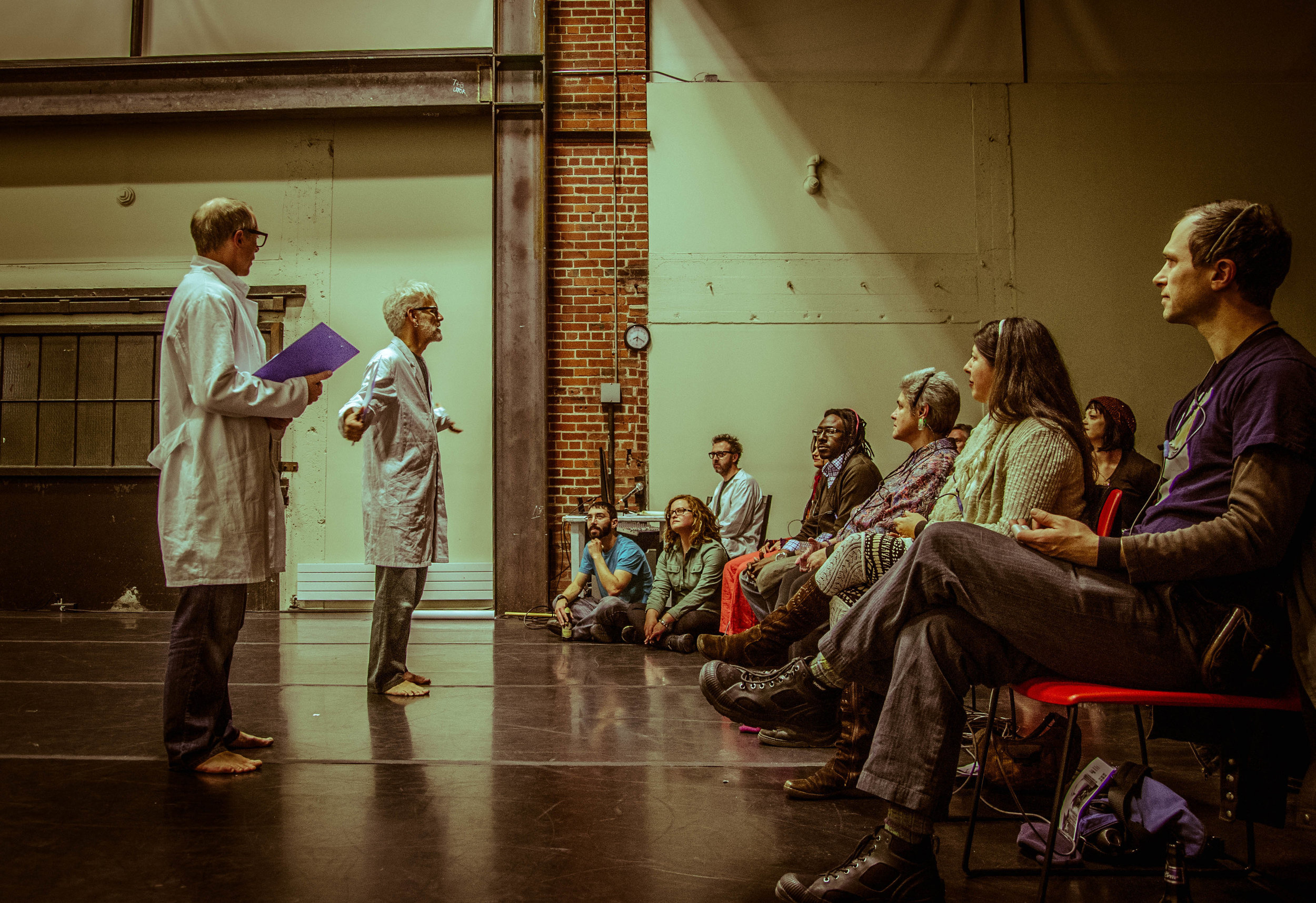 Müller and Curtis, in glasses and lab coats, address an informal audience that is seated in chairs and on the performance space floor. (photo: Robbie Sweeny)