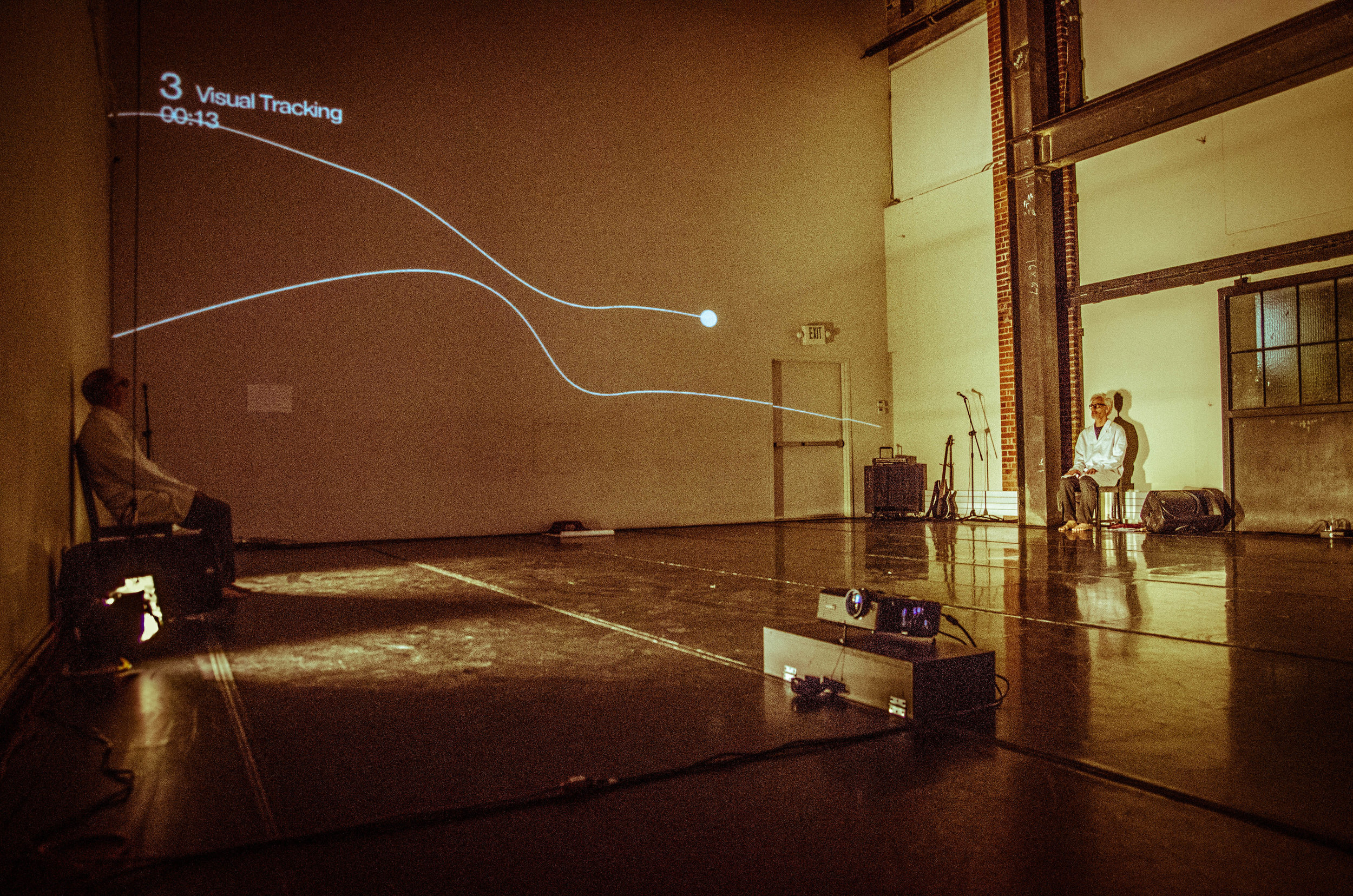 """Müller and Curtis sit on opposite sides of a large white-walled room. Projection on back wall of 2 wavy lines reads """"3 Visual Tracking 00:13."""" (photo: Robbie Sweeny)"""