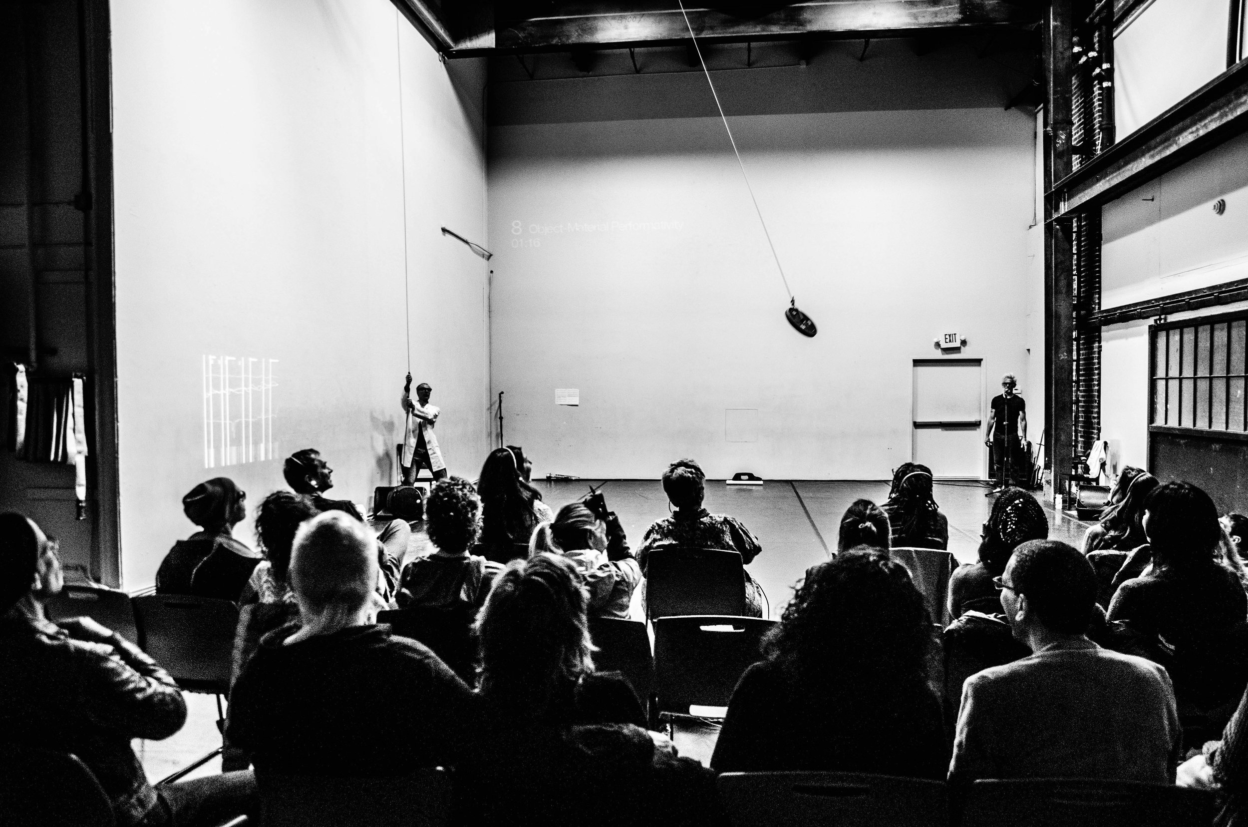 B/W image from audience POV. Curtis at mic. Müller holds rope controlling a large round circular object that swings above the stage. (photo: Robbie Sweeny)