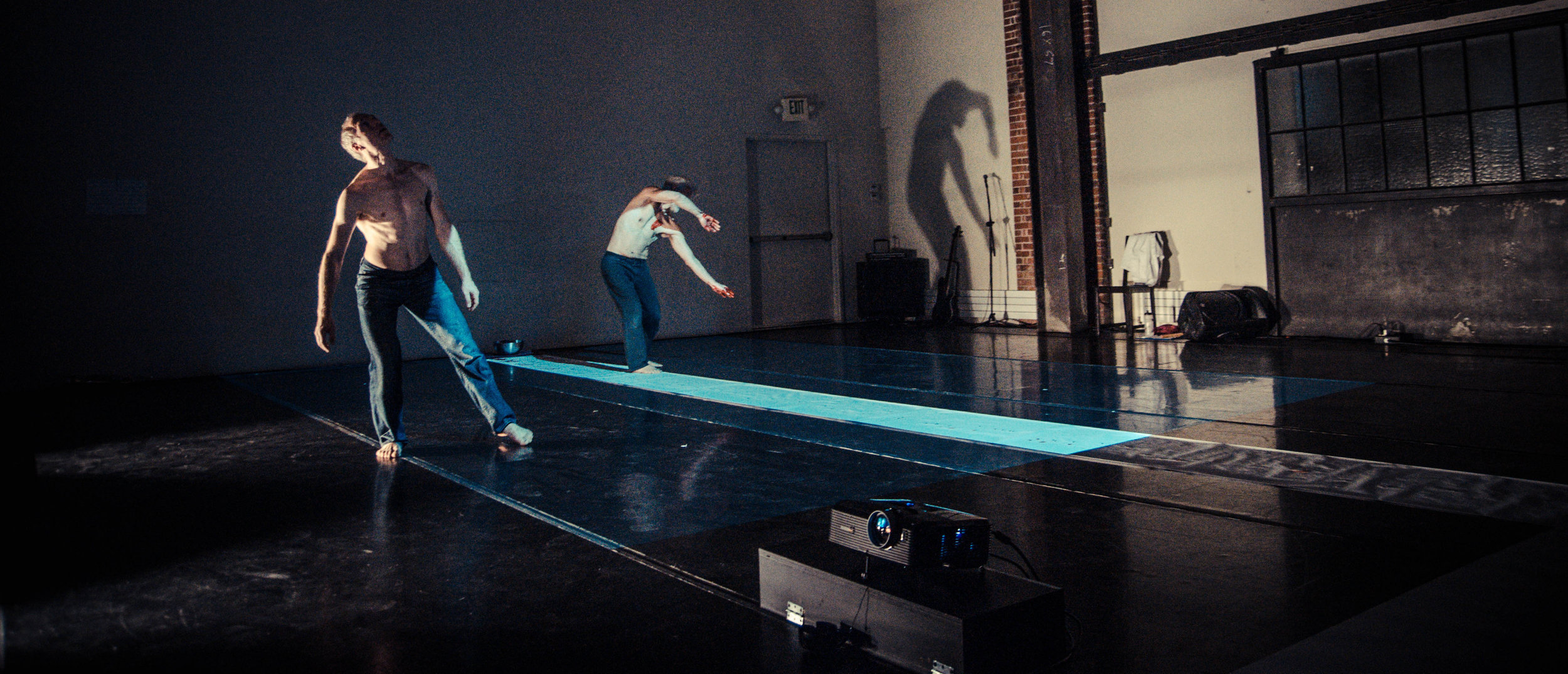 Müller, shirtless, arches upper back, while Curtis, upper back arched to side, is lit by a strip of blue light in darkened stage space. (photo: Robbie Sweeny)