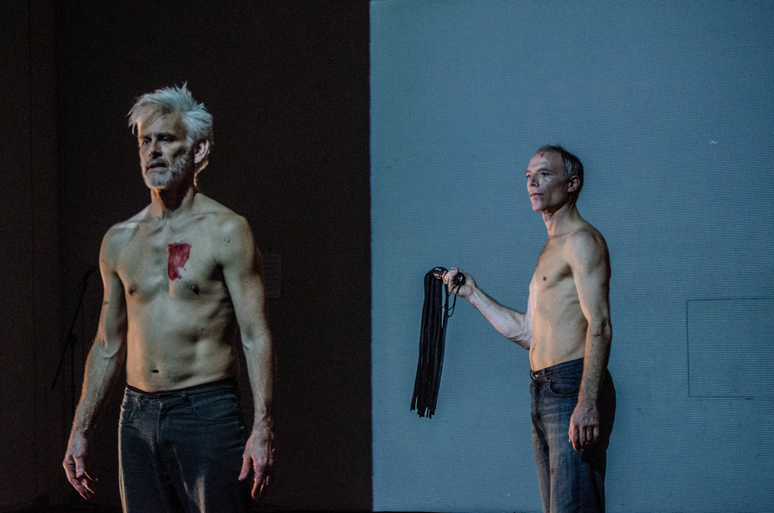 Curtis in foreground, smudge of red over his heart. Müller, behind, holds flogger and looks at Curtis. Both are shirtless. (photo: Robbie Sweeny)