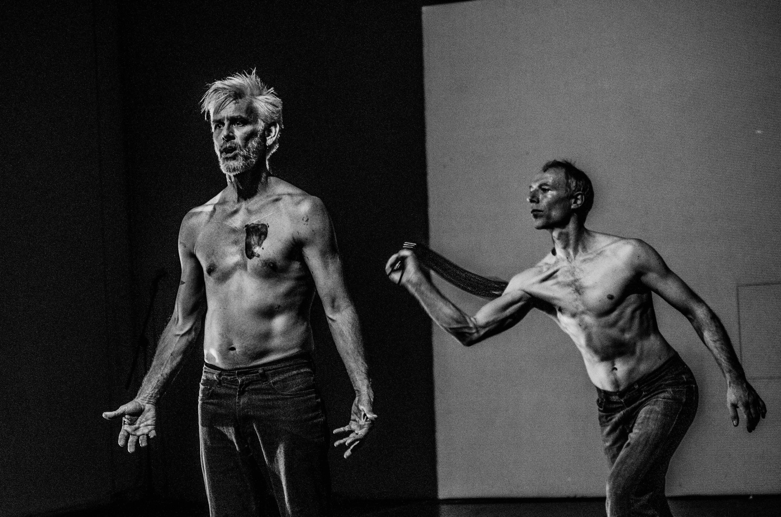 Curtis speaks, hands gesturing at his side, as Müller flogs him from behind. High contrast black and white image. (photo: Robbie Sweeny)