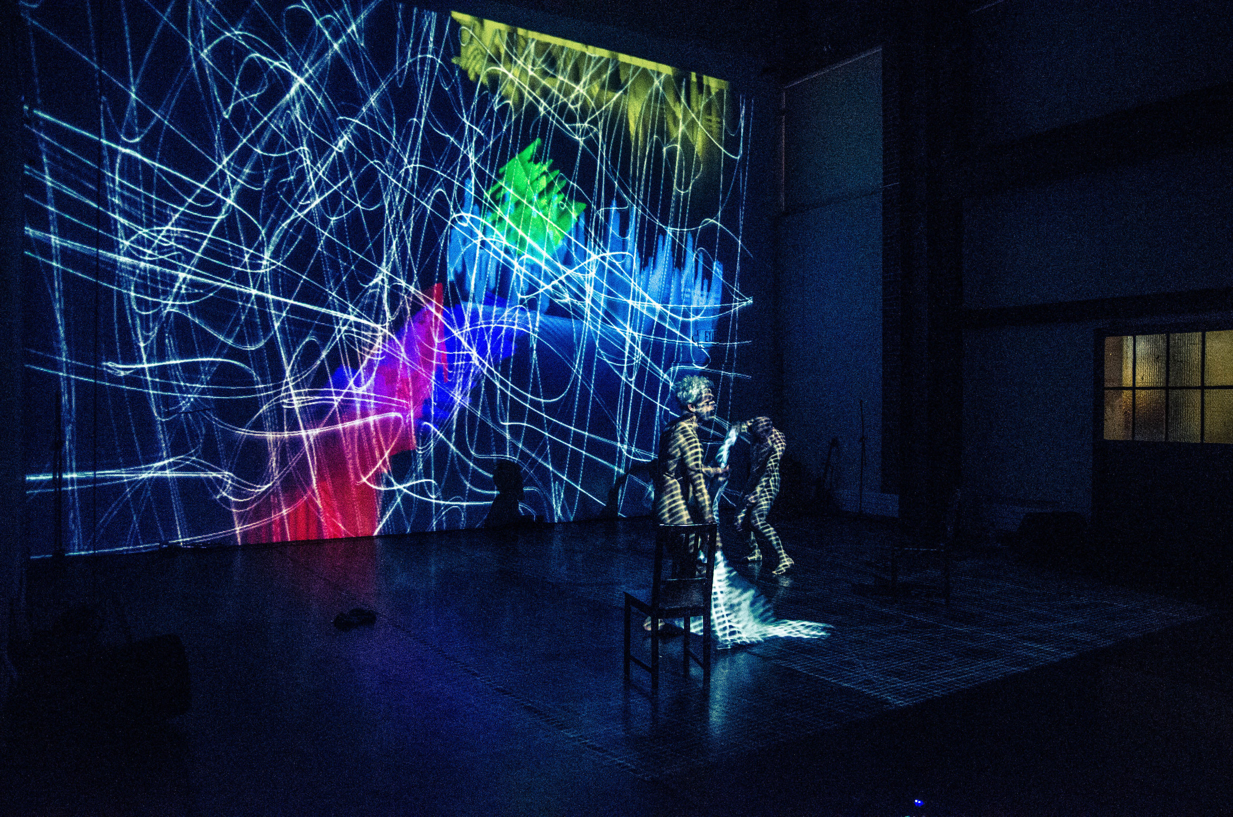 Wild scribbles of brightly colored projections fill the back wall. Curtis and Müller, both nude, bathed in graphic light pattern. (photo: Robbie Sweeny)
