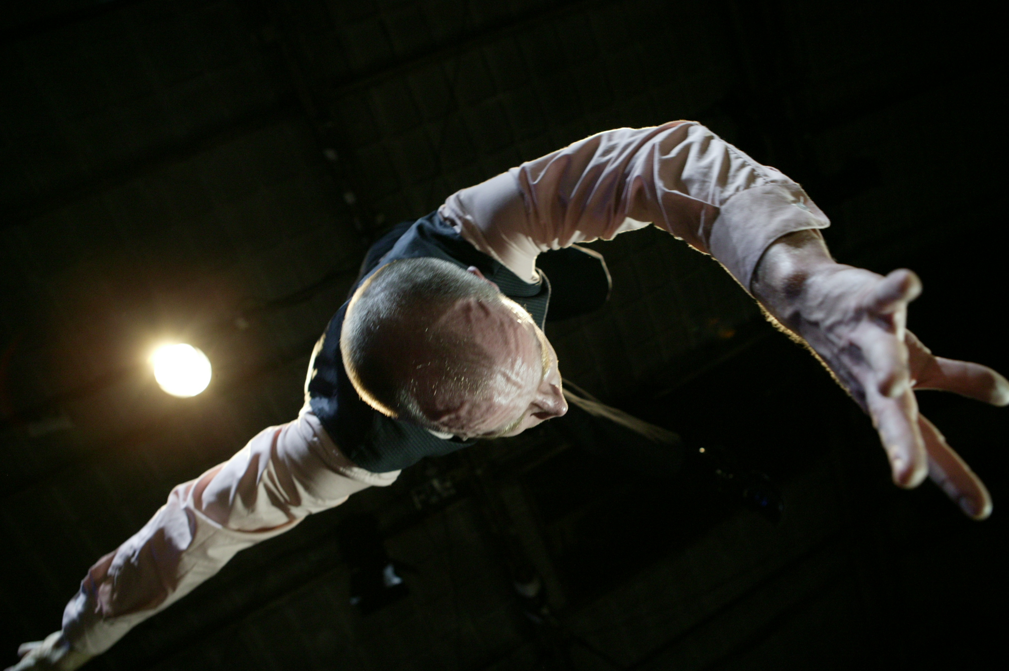 Closeup of Quarrel, in dress shirt and vest with buzz-cut hair, suspended from ceiling above camera. One arm reaches to camera. (photo: Sven Hagolani)