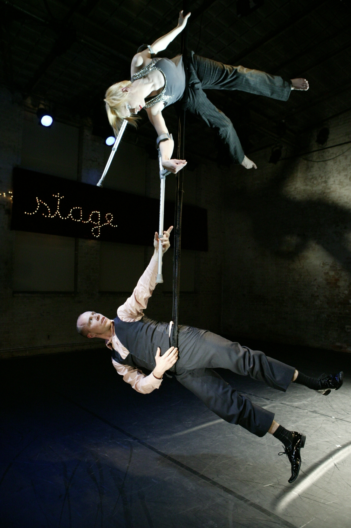 Cunningham hangs above Quarrel, both on aerial ropes. She holds 2 crutches; he grasps the end of one. (photo: Sven Hagolani)