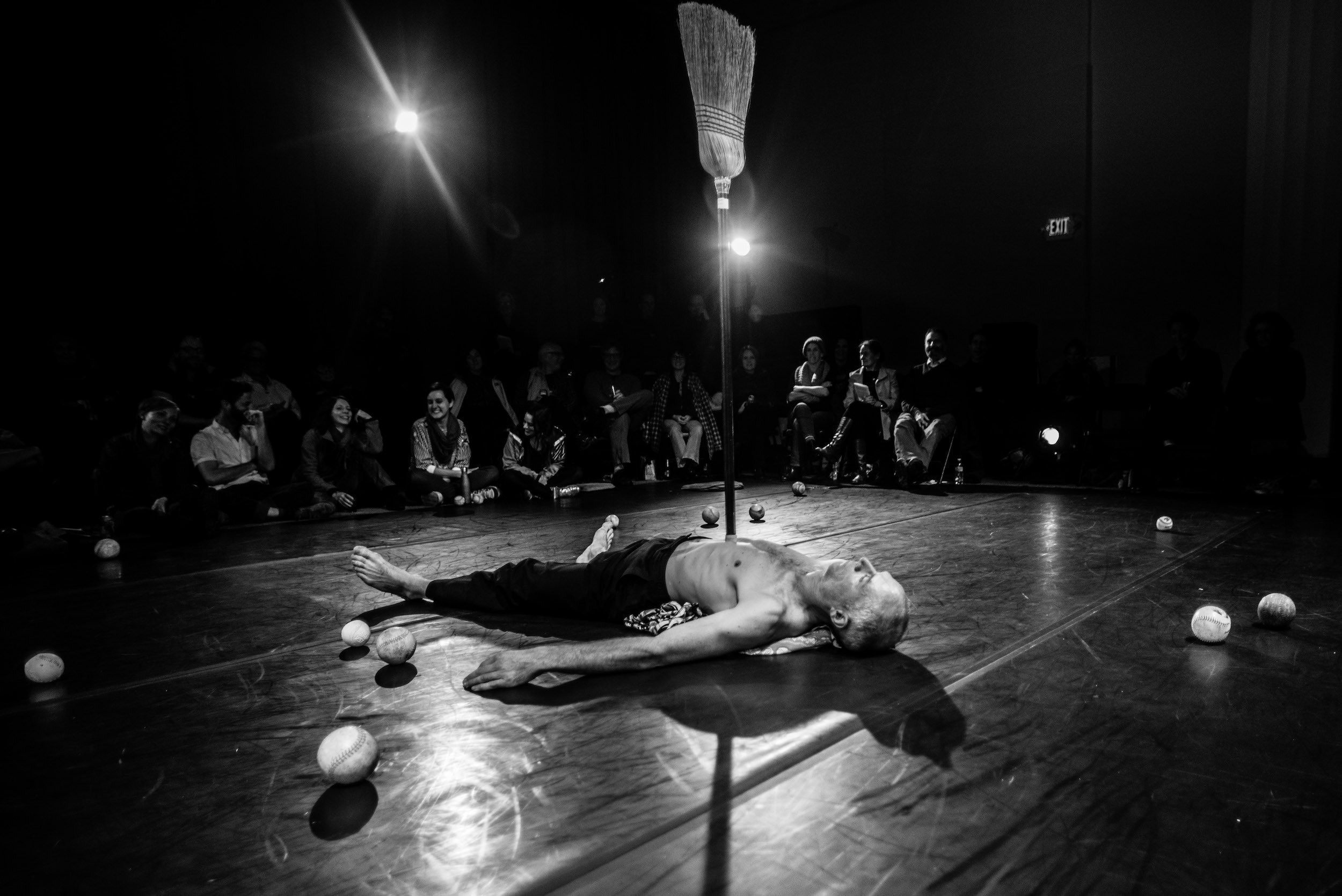 Müller, shirtless, lies on floor balancing broom vertically from his belly. Beyond, a row of audience sit on the floor, smiling. (photo: Robbie Sweeny)