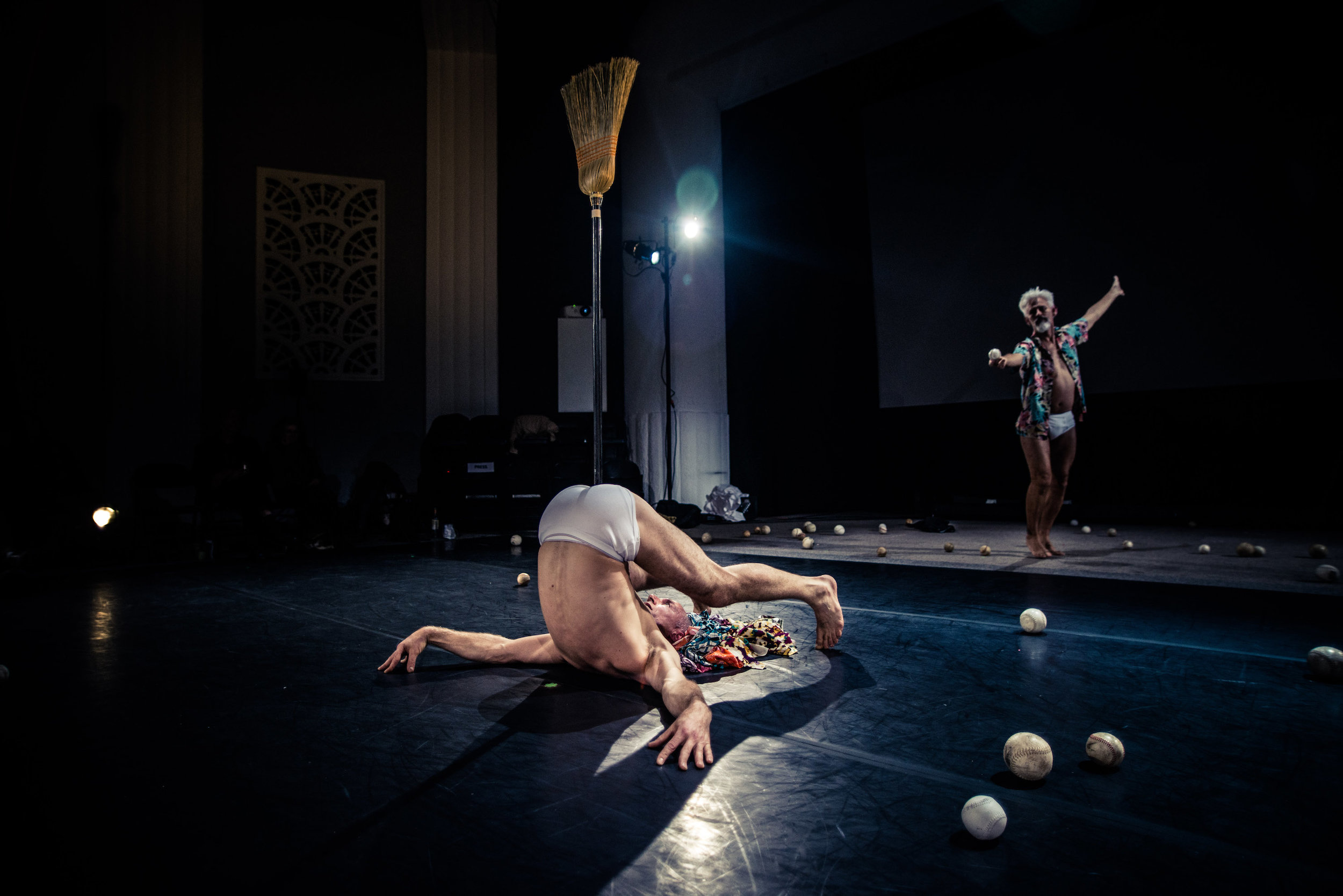 Curtis gestures with flourish toward Müller, who balances a broom from his anus, in  plow pose wearing white underwear. (photo: Robbie Sweeny)