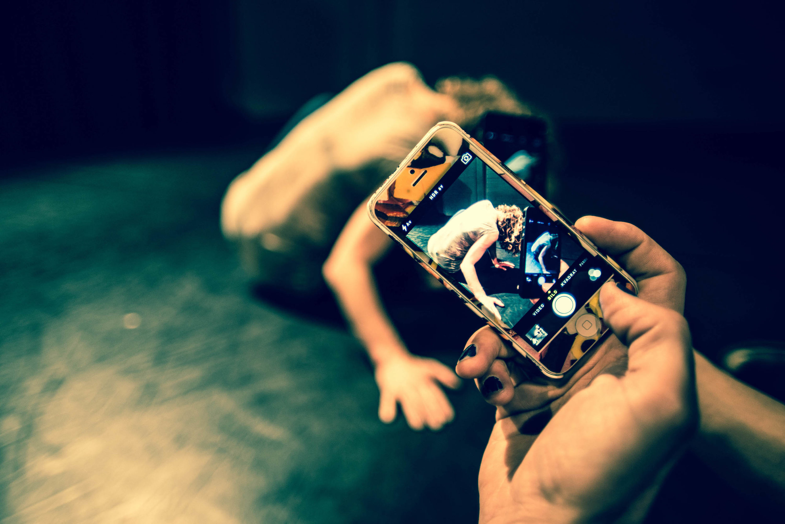 A hand holds a smartphone in foreground: Crain, visible through phone's camera, sits with back to camera, blonde curls covering face. (photo: Robbie Sweeny)