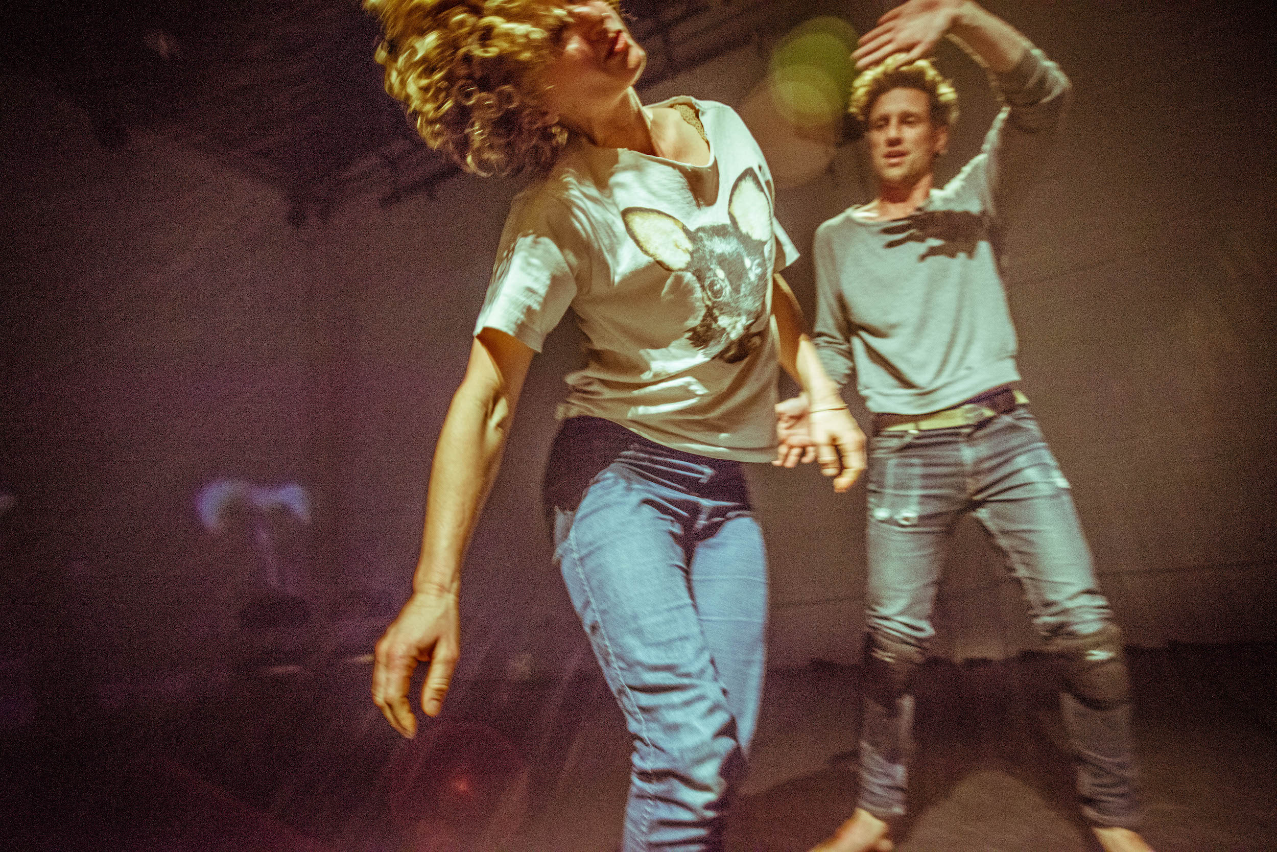 Action shot of curly-headed Crain (in chihuahua tee) & Anderson (in worn jeans and knee pads) swaying with streaks of light. (photo: Robbie Sweeny)