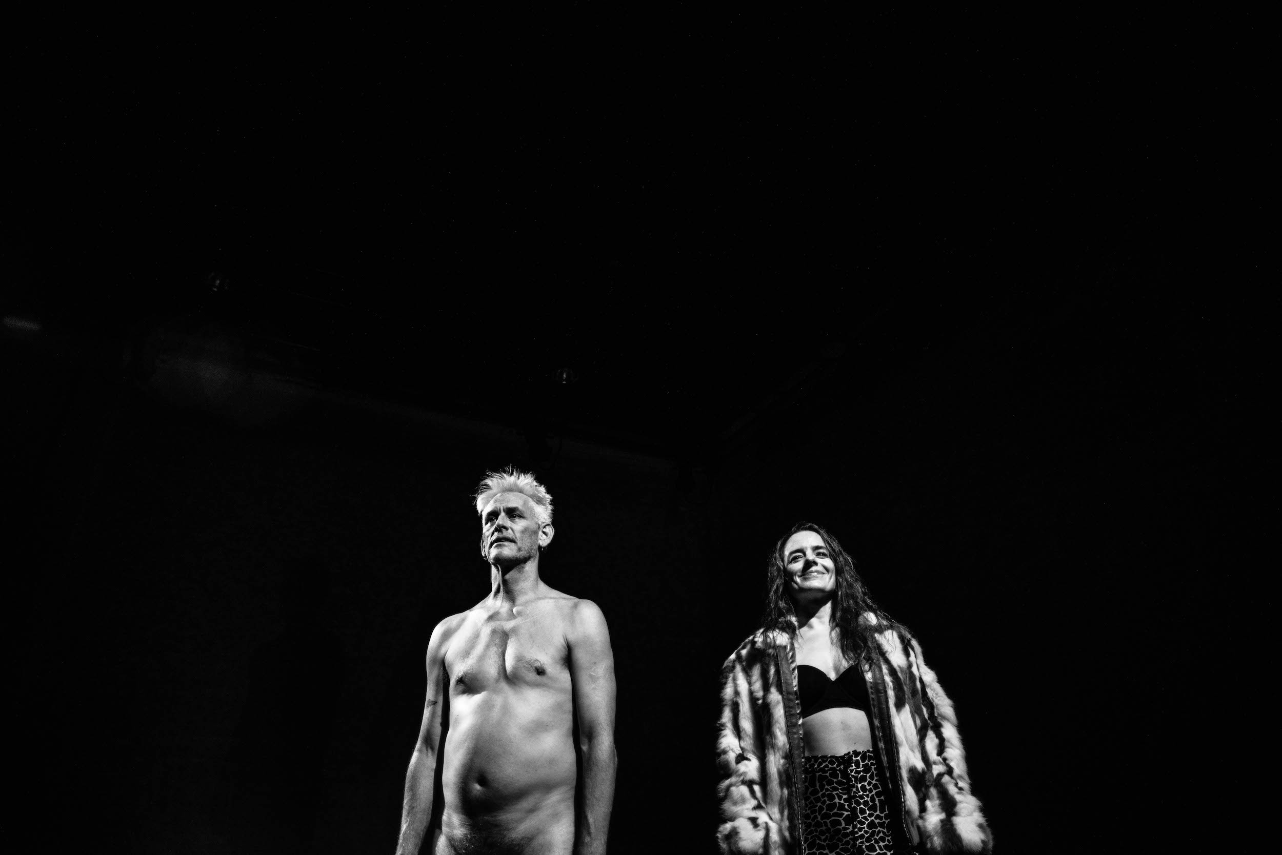 Black-white image of Curtis (nude) and Dichter (in black bra and fur coat) against black background, image cropped at the hip. (photo: Robbie Sweeny)